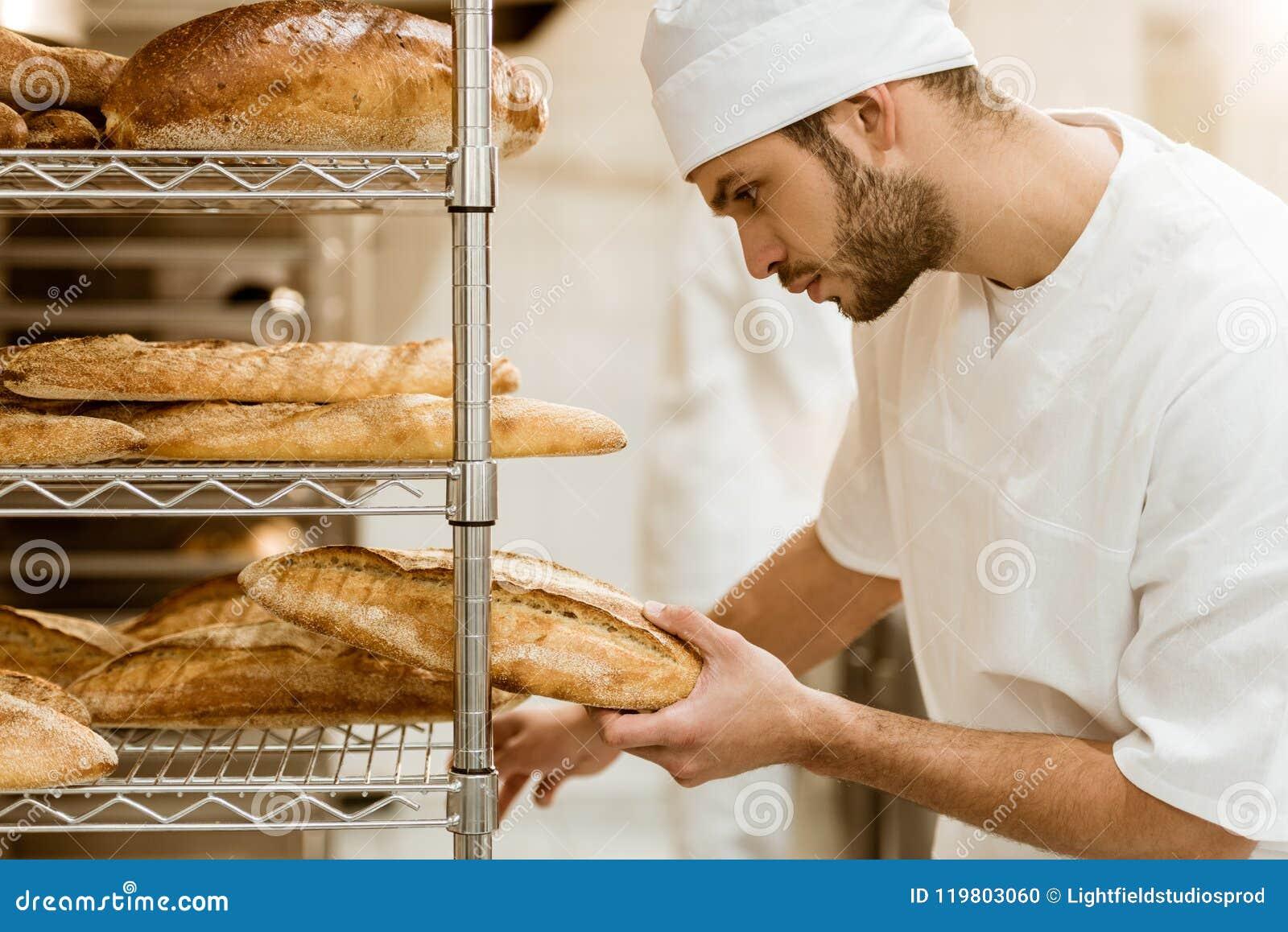 Zijaanzicht van knappe bakker die vers brood op plank zetten