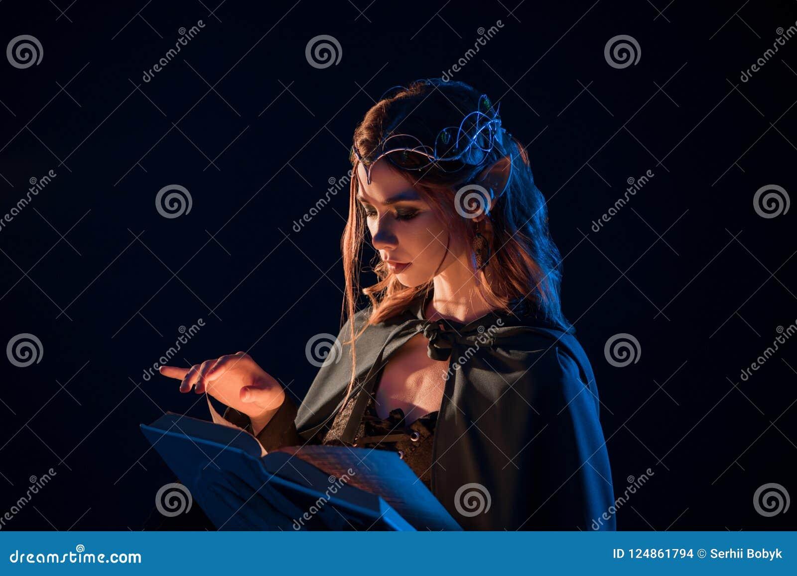 Zijaanzicht van mysticus vrouwelijk mooi elf die magisch boek in duisternis lezen