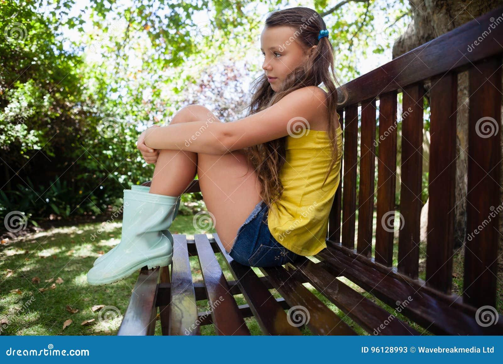 Zijaanzicht van nadenkende meisjeszitting op houten bank