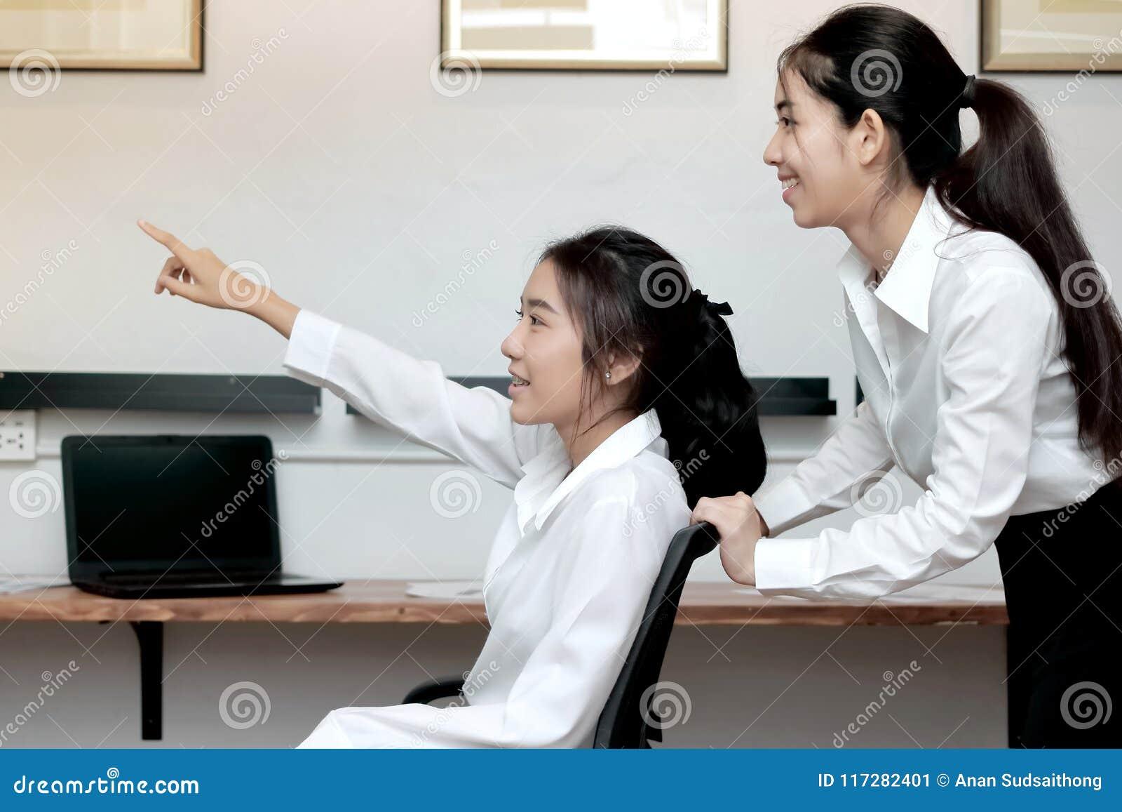 Zijaanzicht van vrolijke Aziatische bedrijfsvrouw die pret samen in bureau hebben