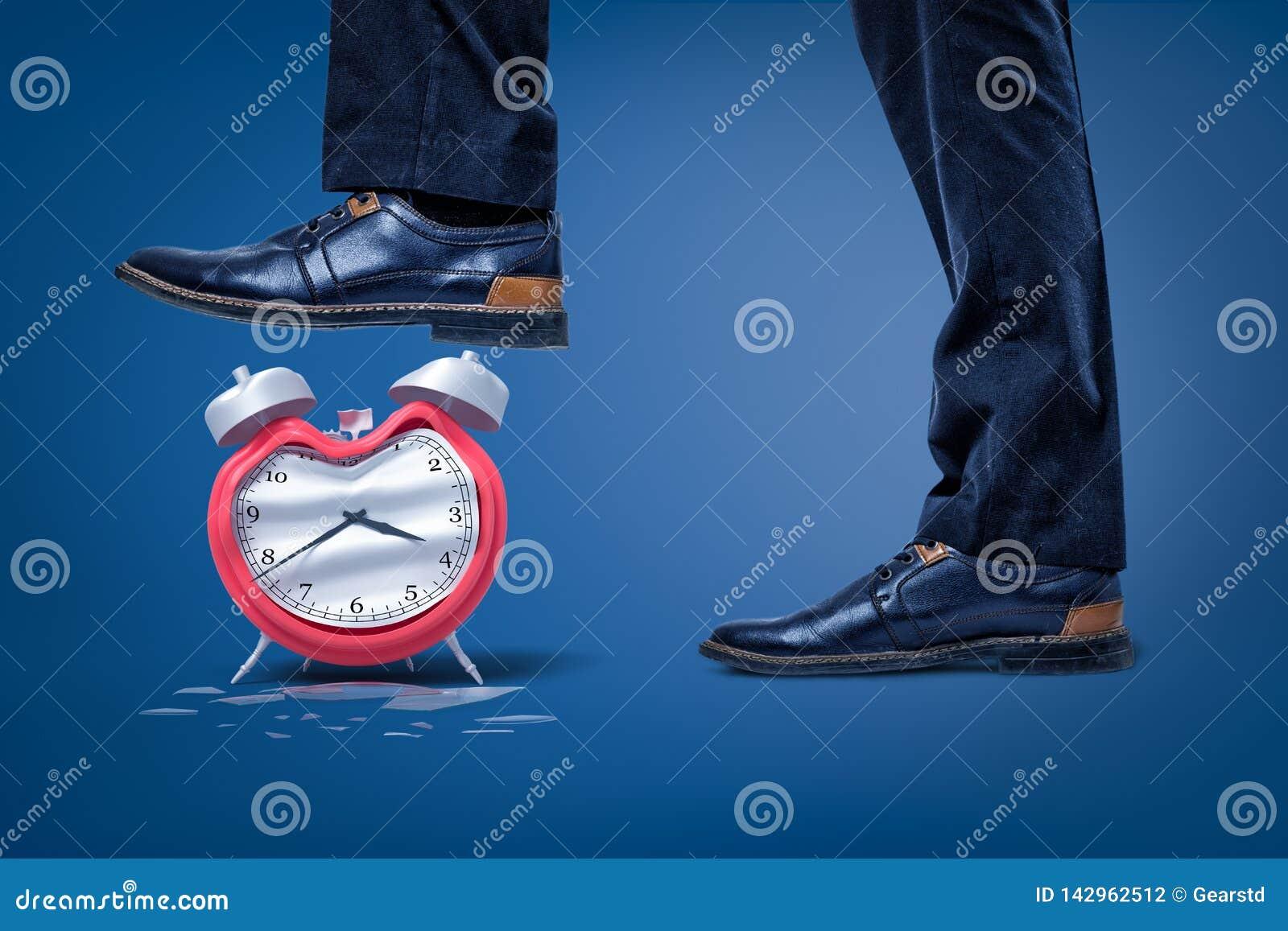 Zijclose-up van man voeten, ??n die voet aan verbrijzeling gebroken gebogen wekker wordt opgeheven