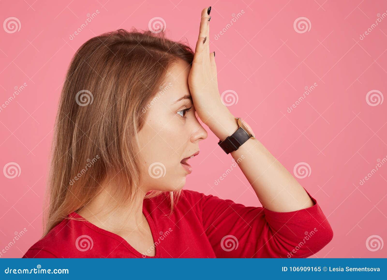 Zijdelings houdt het portret van mooi wijfje hand op voorhoofd, herinnert zich om belangrijk iets te doen, aantoont haar slecht g