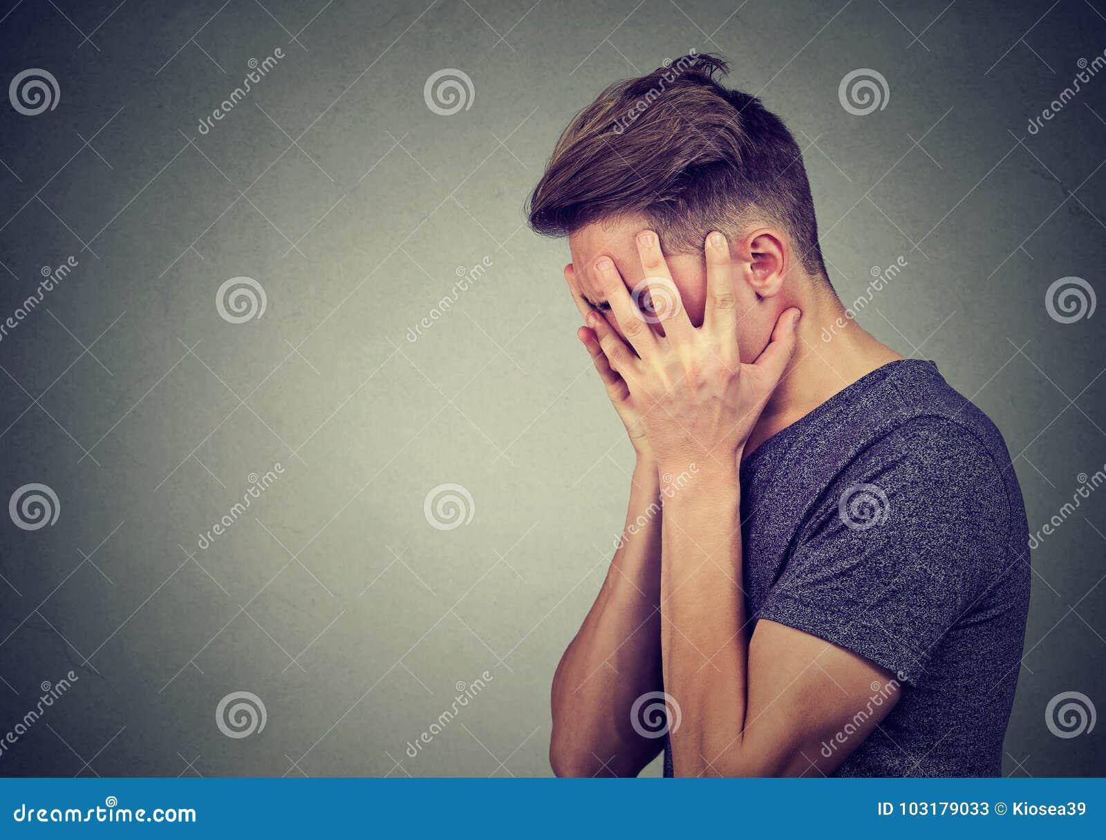Zijprofiel van een droevige jonge mens die met handen op gezicht neer kijken Depressie en bezorgdheidswanorde