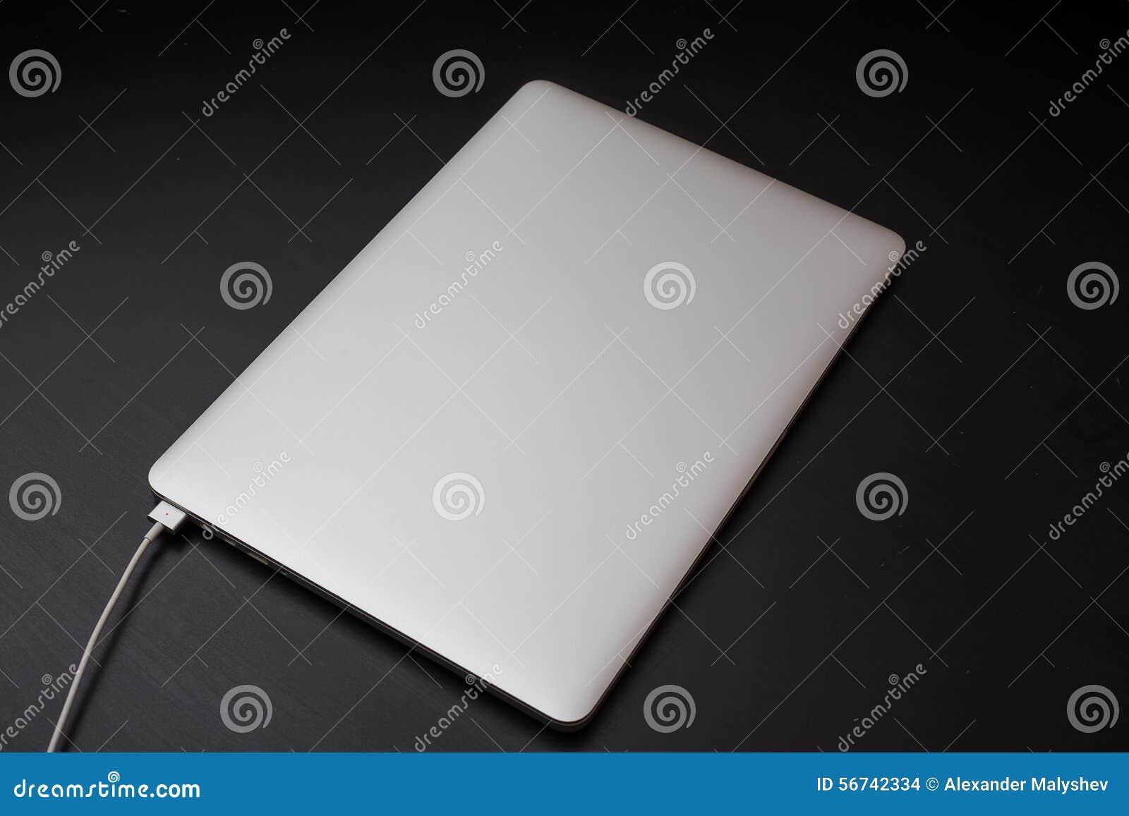 Zilveren laptop die door magnetische schakelaar op de zwarte houten achtergrond laden