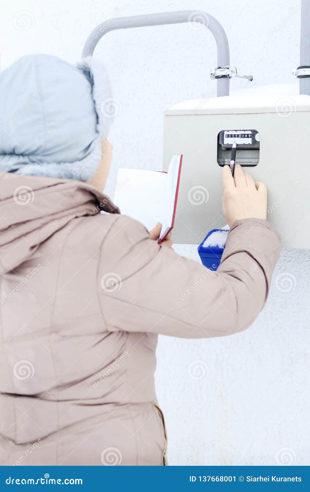 Zima, śnieg, zimno dziewczyna inżynier pracownik nagrywa czytania ciśnieniowi wymierniki i czujniki Lokalizują