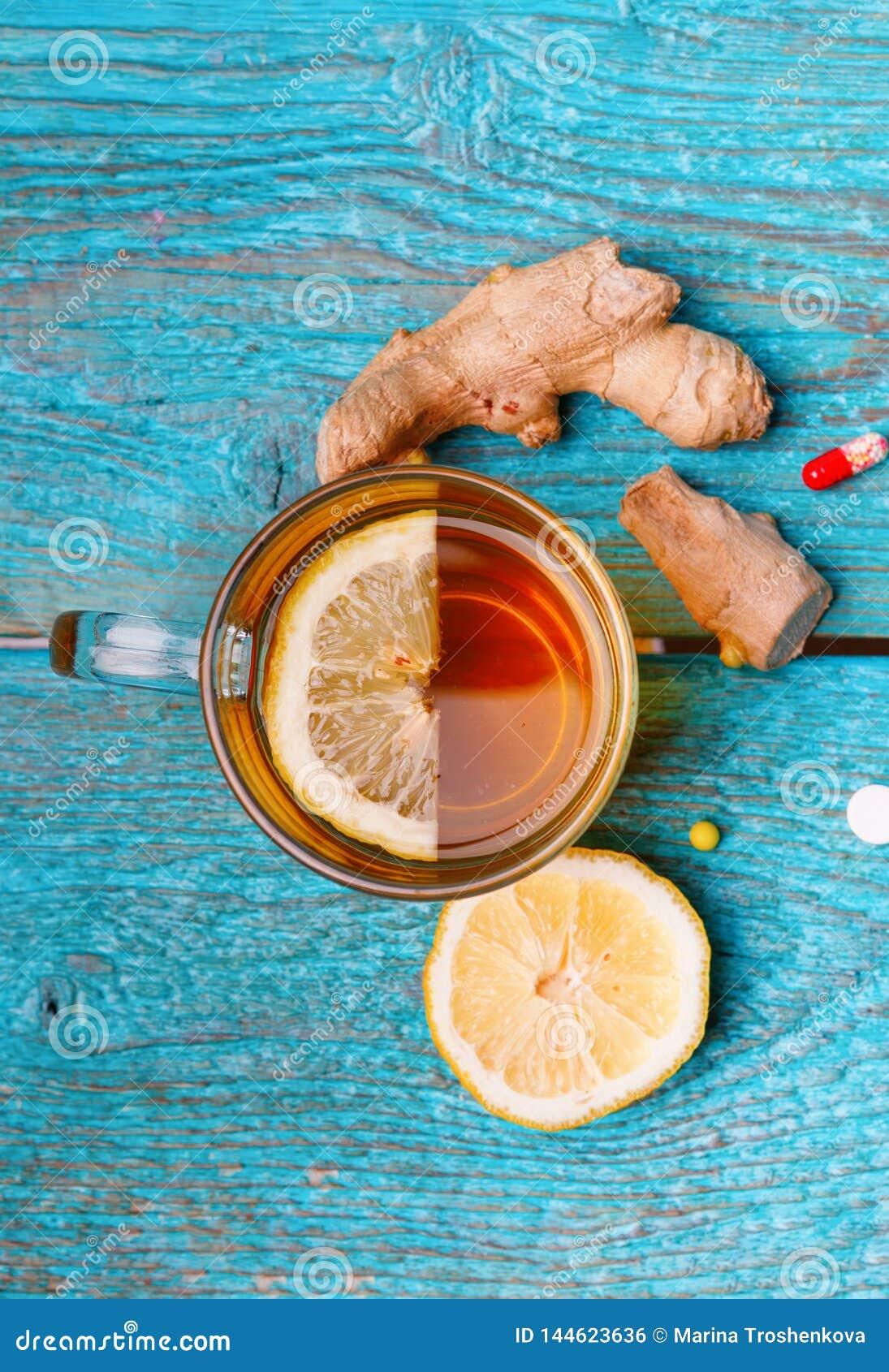 Zimne medycyny, herbata, cytryna i imbir na drewnianym b??kitnym tle,