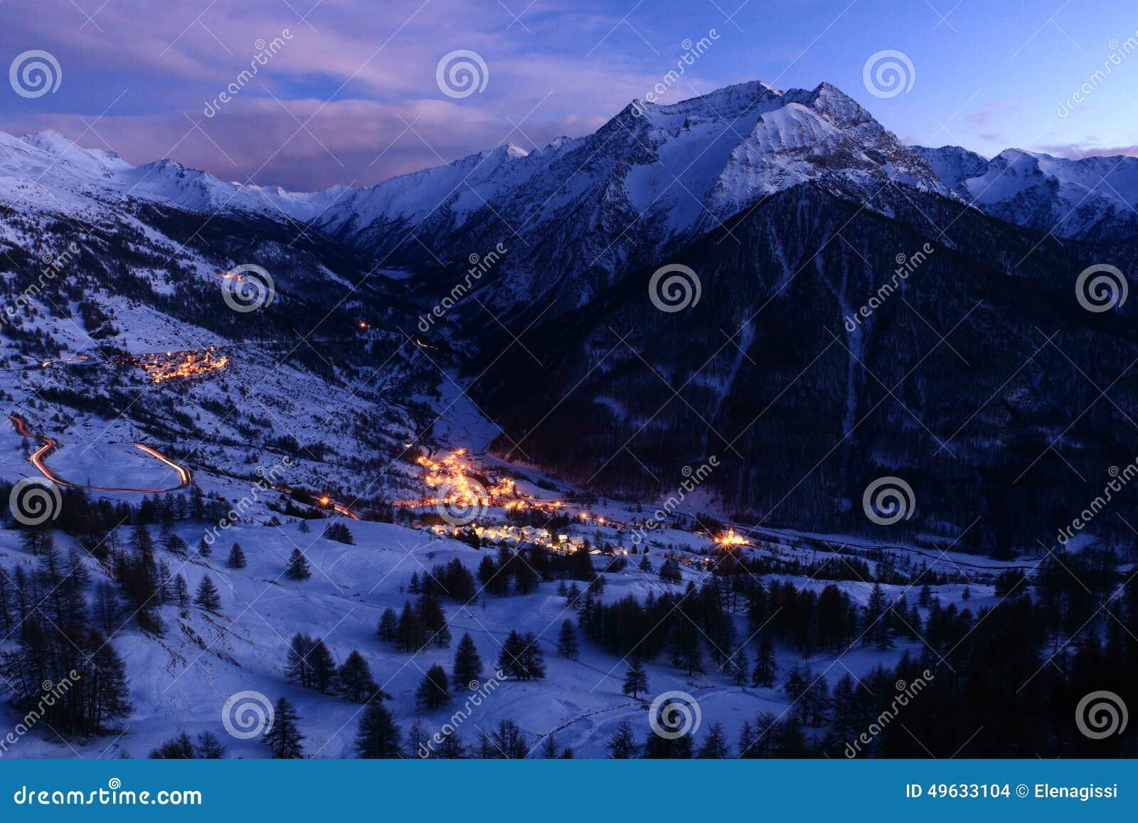 Zimy góry krajobraz przy półmrokiem z śniegiem i wioską