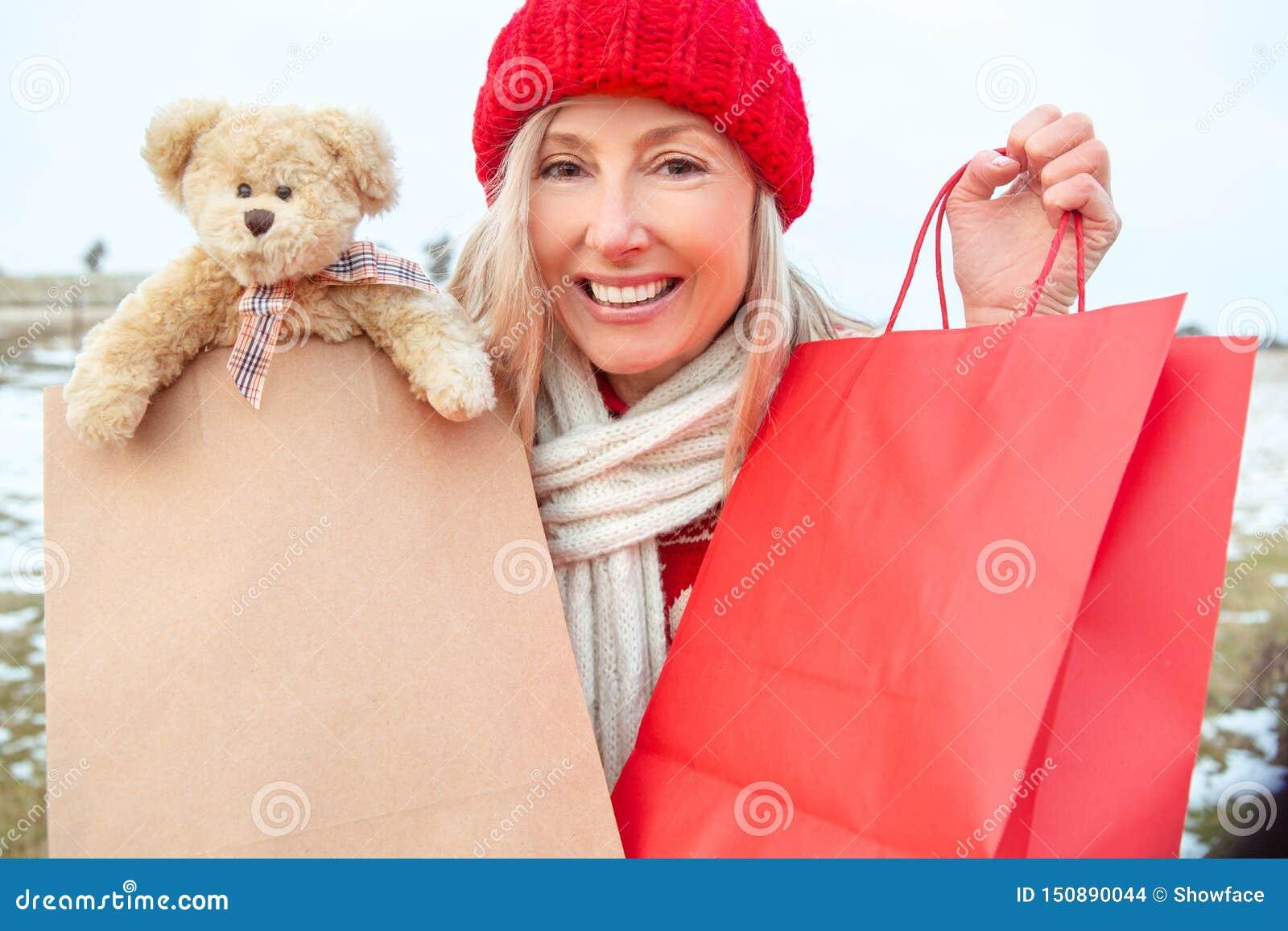 Zimy kobiety mienia handlu detalicznego prezenta lub zakupy torby
