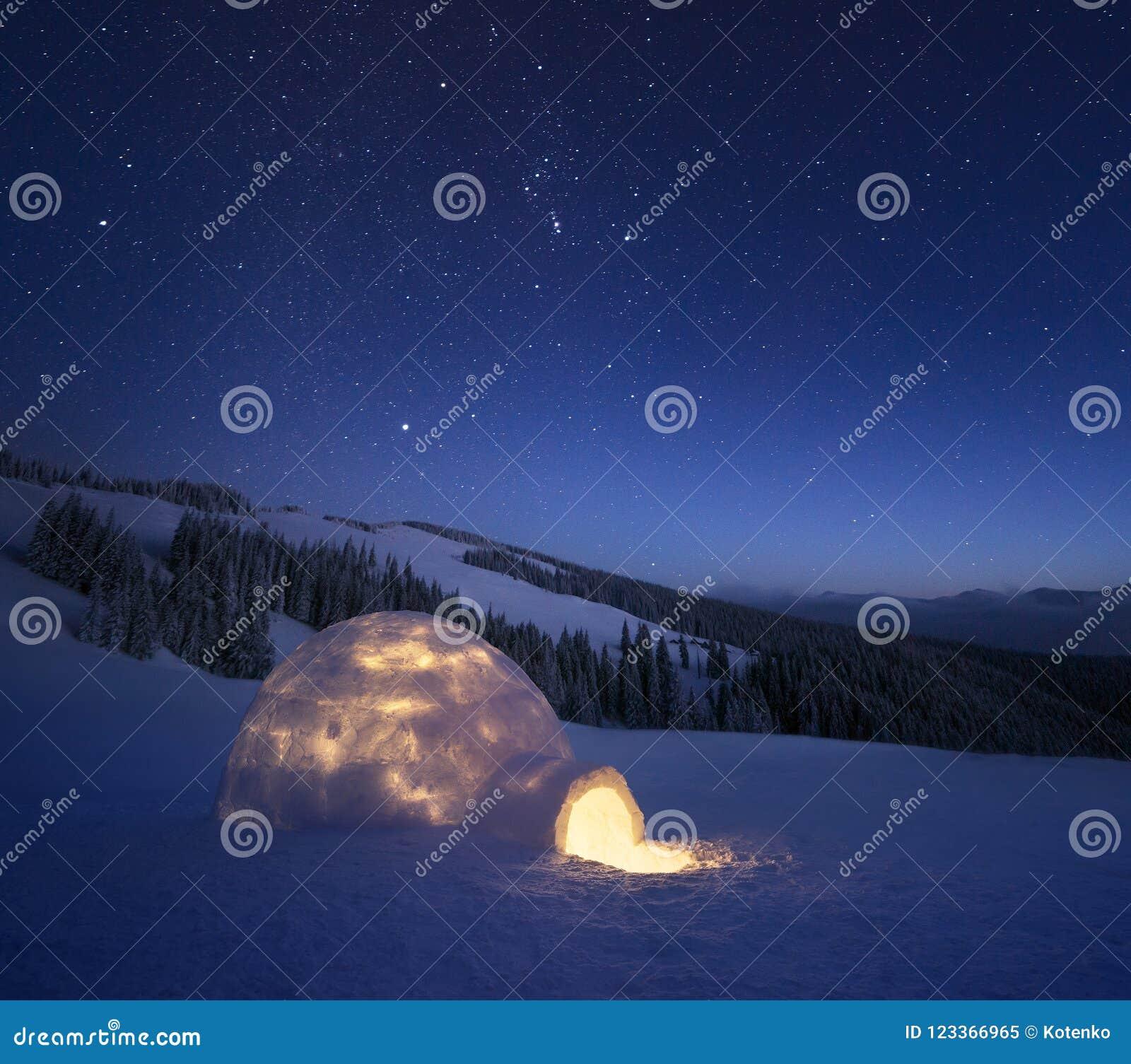 Zimy nocy krajobraz z śnieżnym igloo i gwiaździstym niebem