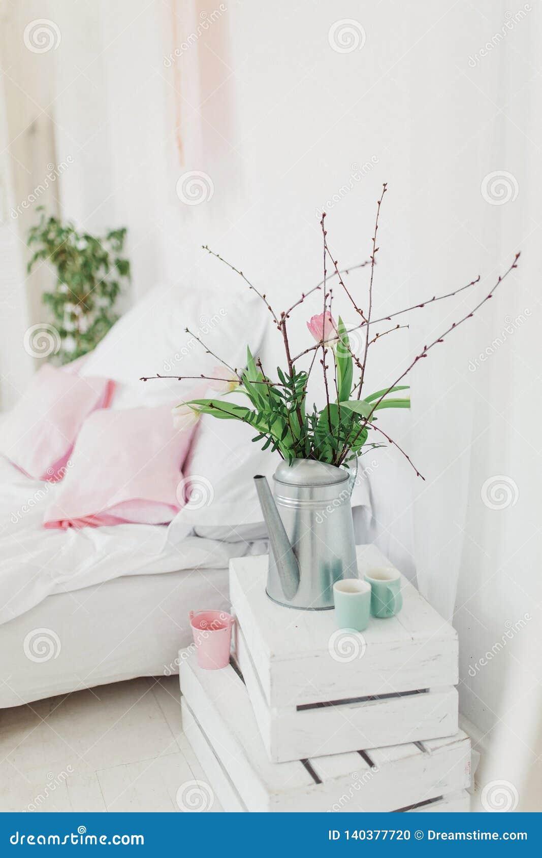 Zink som bevattnar kan med rosa tulpan över vit bakgrund i sovrum