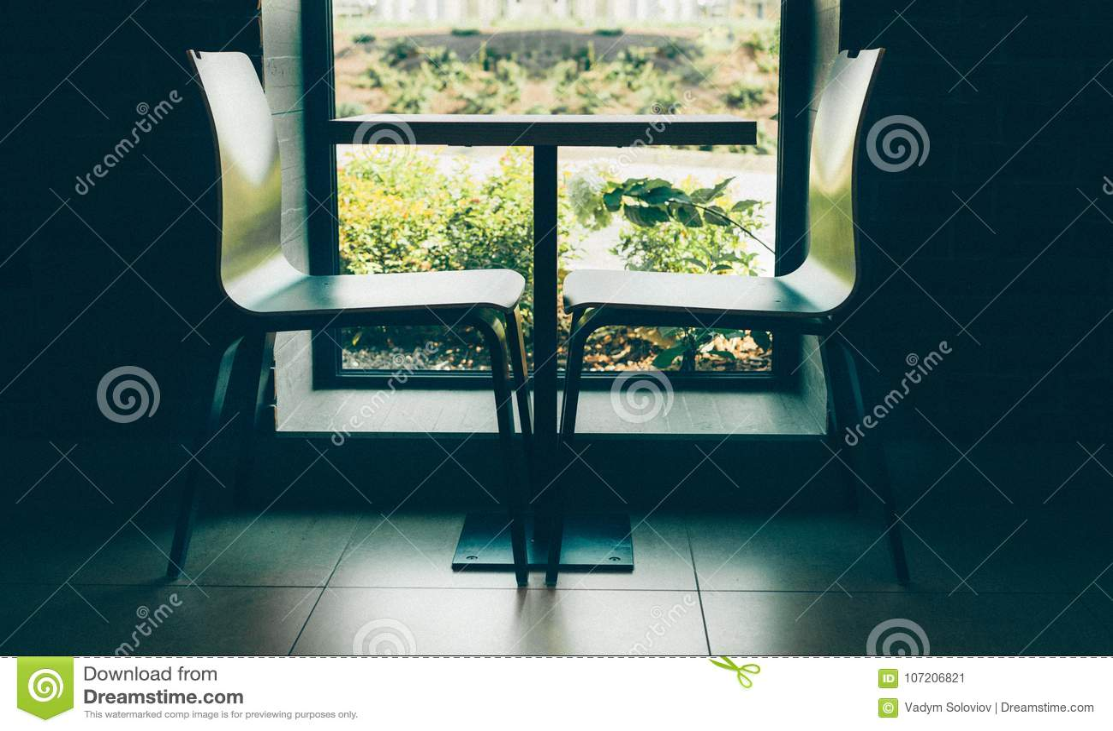 Zit moderne stijl twee dichtbij de leuke kleine lijst voor dichtbij het venster met bakstenen muur zwart-wit binnenlands schot