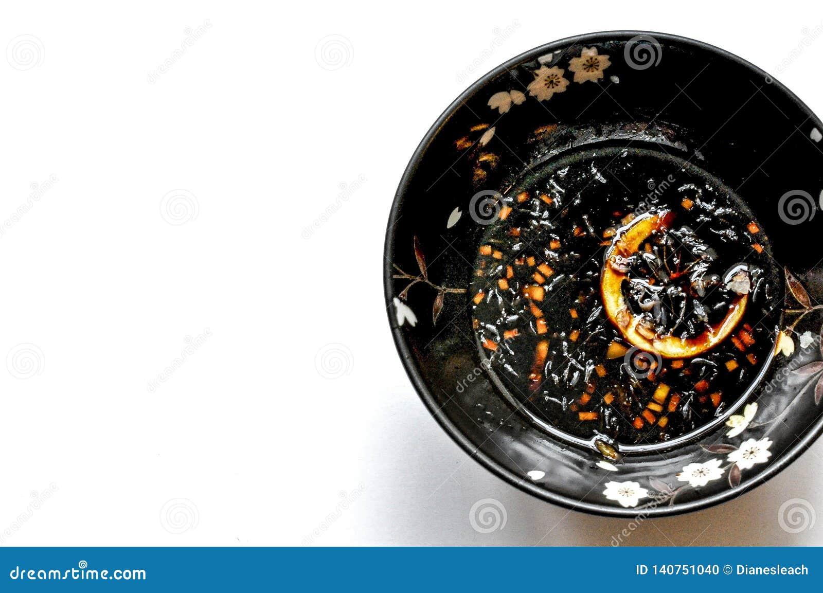 Zitronensojabohnenöldip in einer geblühten schwarzen Schüssel, Draufsicht, weißer Hintergrund