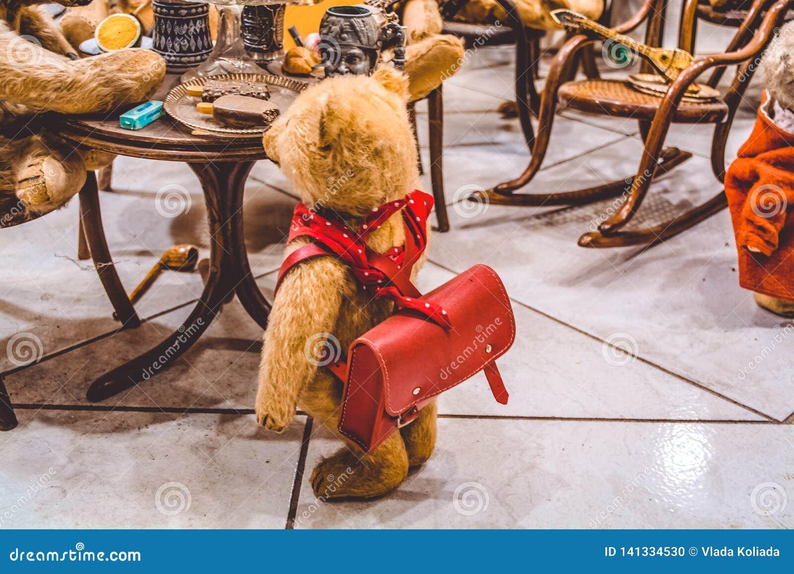 Zitten de Teddy bruine beren bij een lijst en eten roomijs, en naderen hen het jonge geitje met een rugzak Tentoonstelling van sp