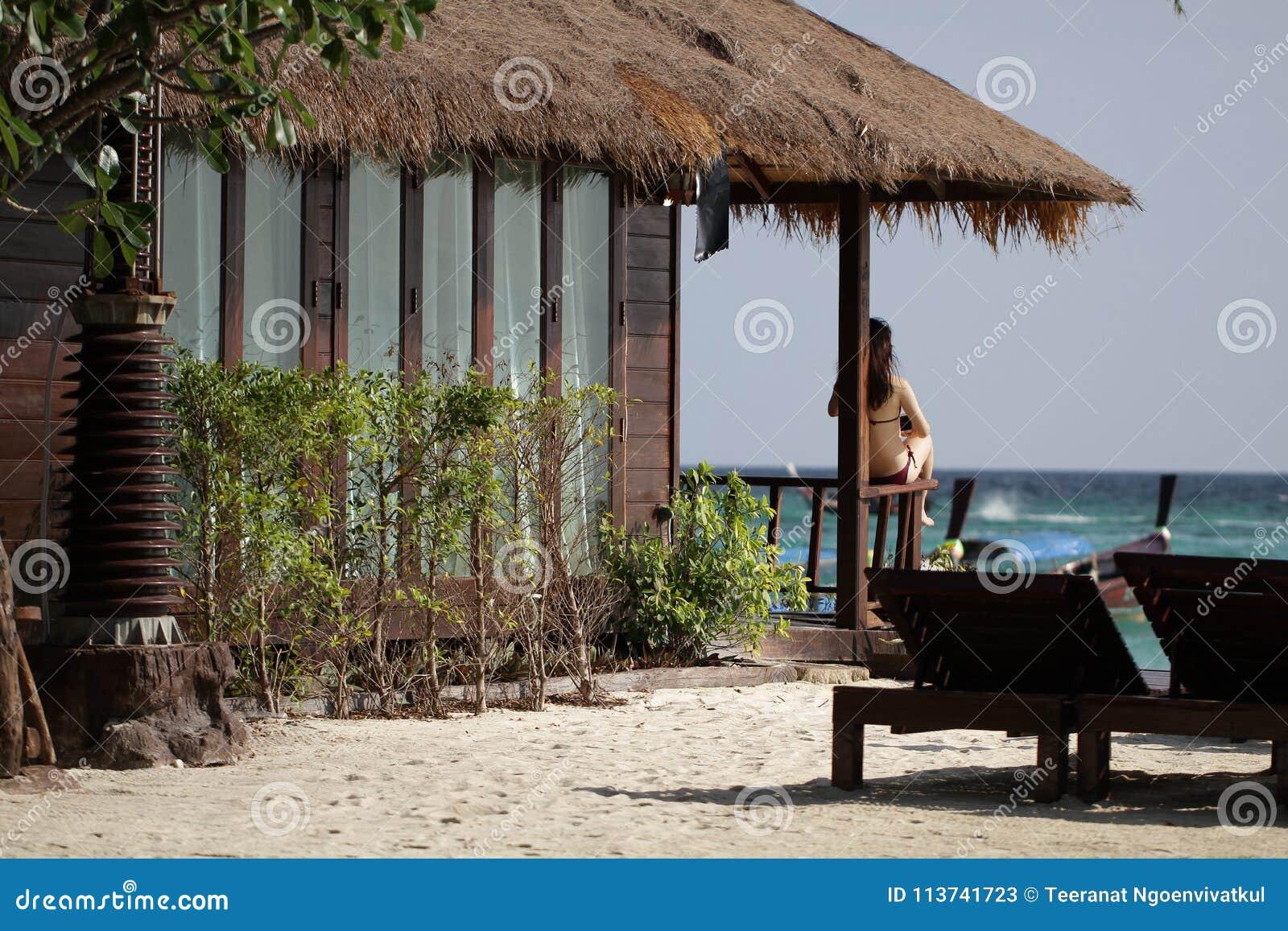 Zitting van de portret de jonge sexy Aziatische vrouwelijke bruine bikini voor luxeaard ingezeten op idyllische de draairug van d