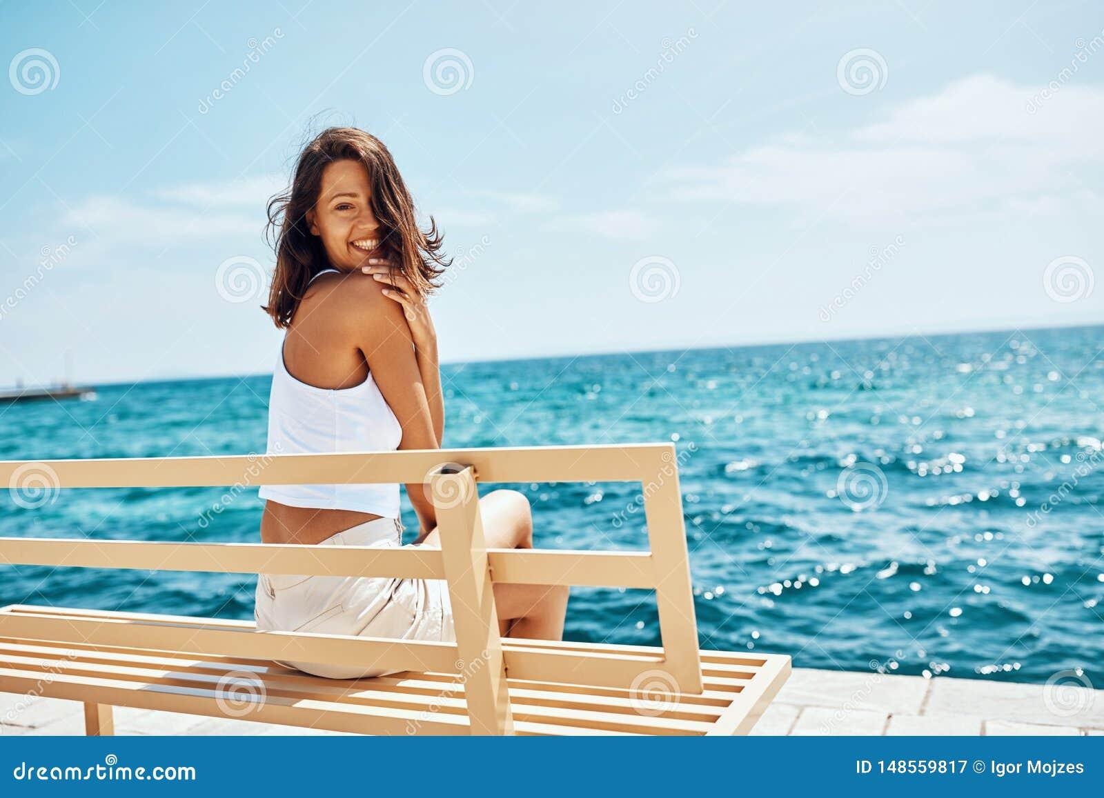 Zitting van het de vakantie de concept-Mooie meisje van het de zomerstrand op bank dichtbij het strand