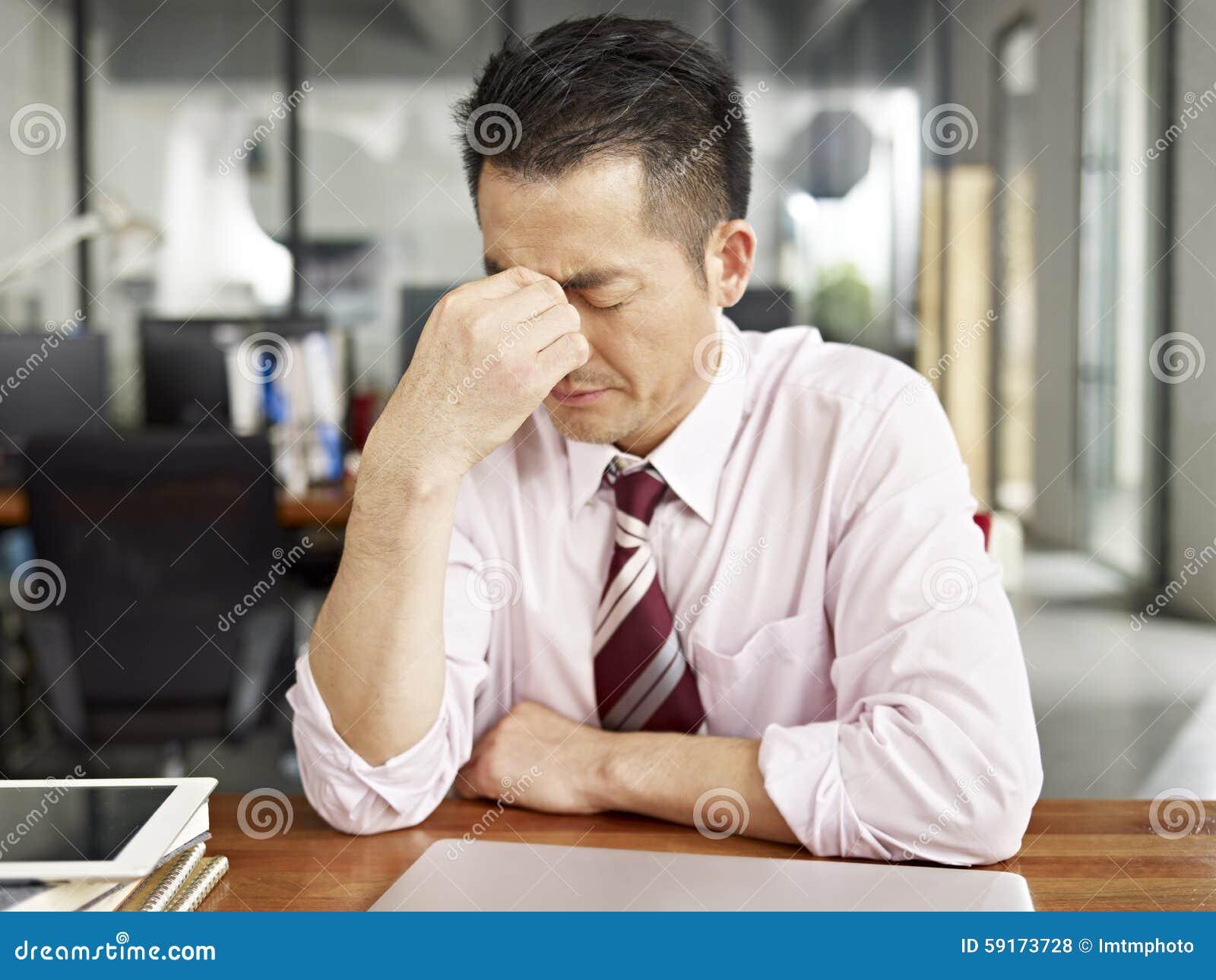 Zmęczona azjatykcia biznesowa osoba