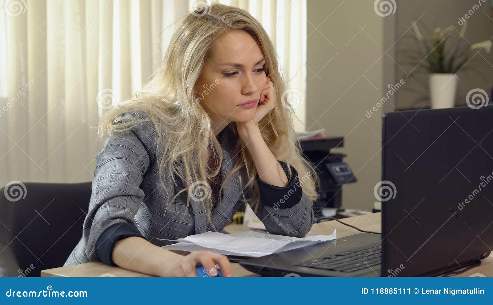 Zmęczona blondynki kobieta spada uśpiony przy miejscem pracy w biurze