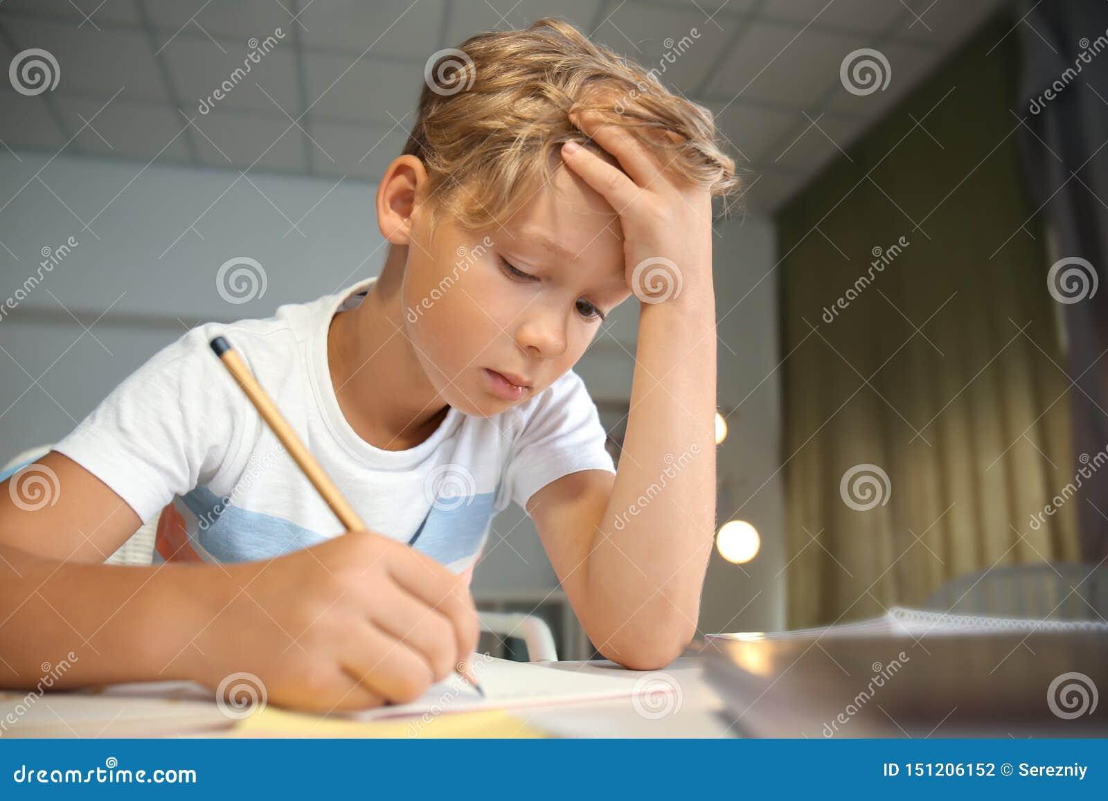 Zmęczona chłopiec robi jego lekcjom w domu