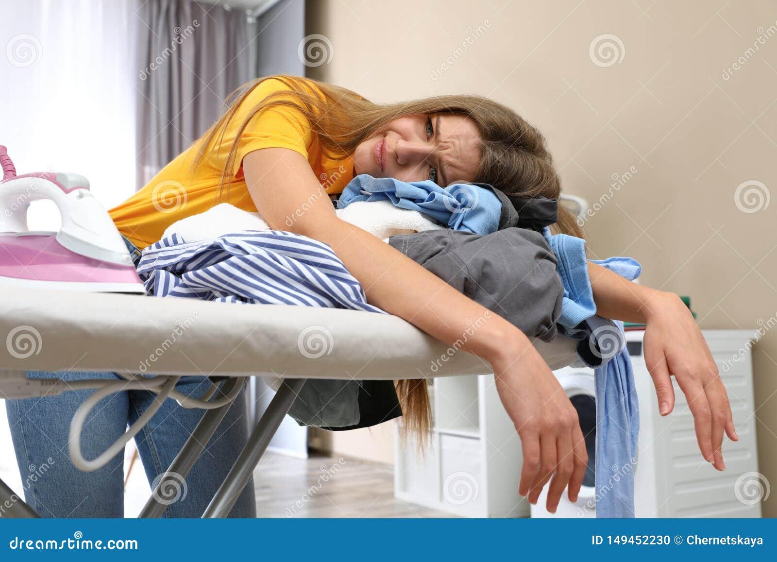 Zmęczona kobieta opiera na prasowanie desce z odziewa