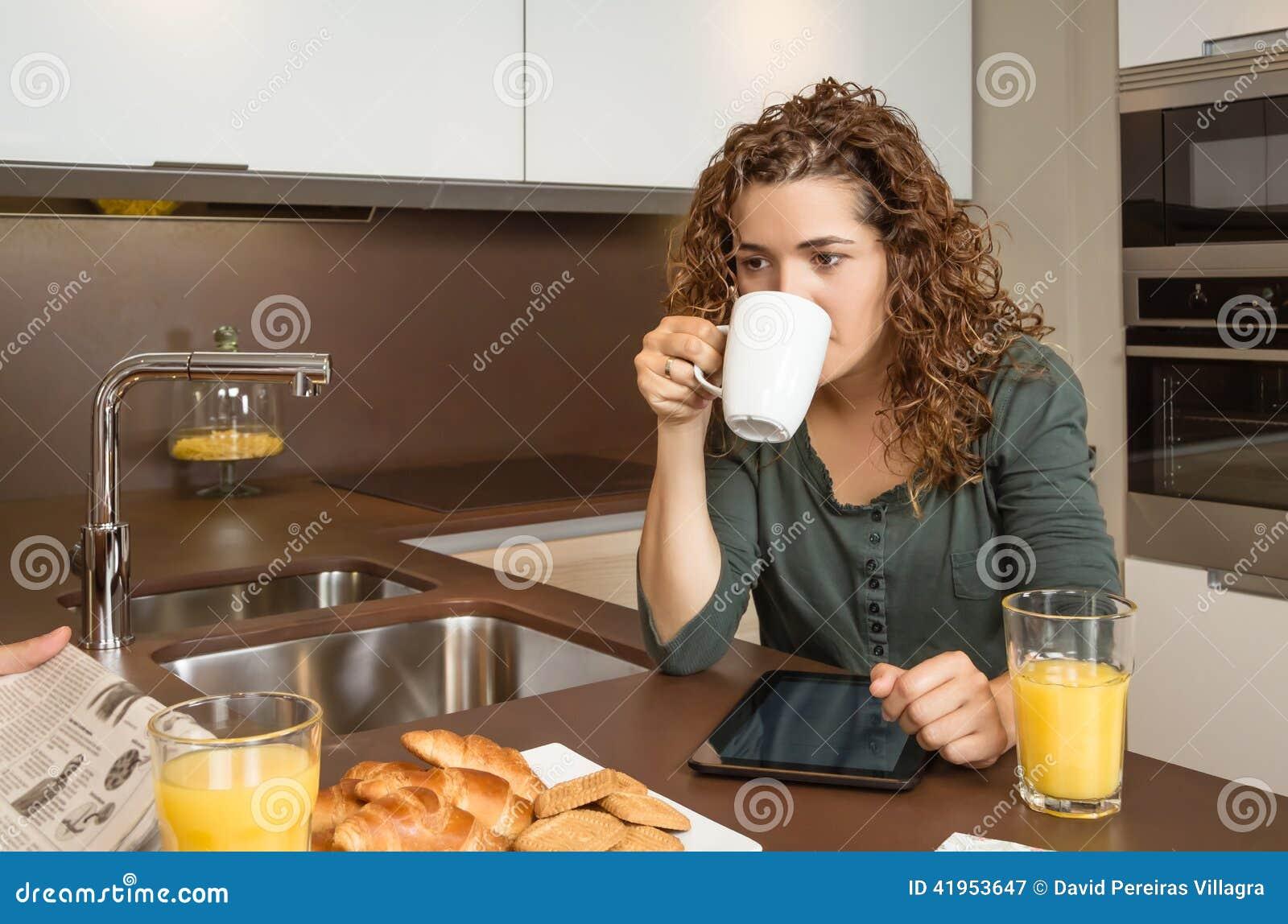 Zmęczona młoda dziewczyna z filiżanką kawy w śniadaniu