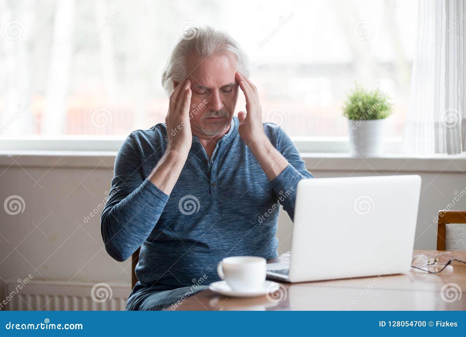 Zmęczone starszego mężczyzna wzruszające świątynie czuje migrenę pracuje na losie angeles