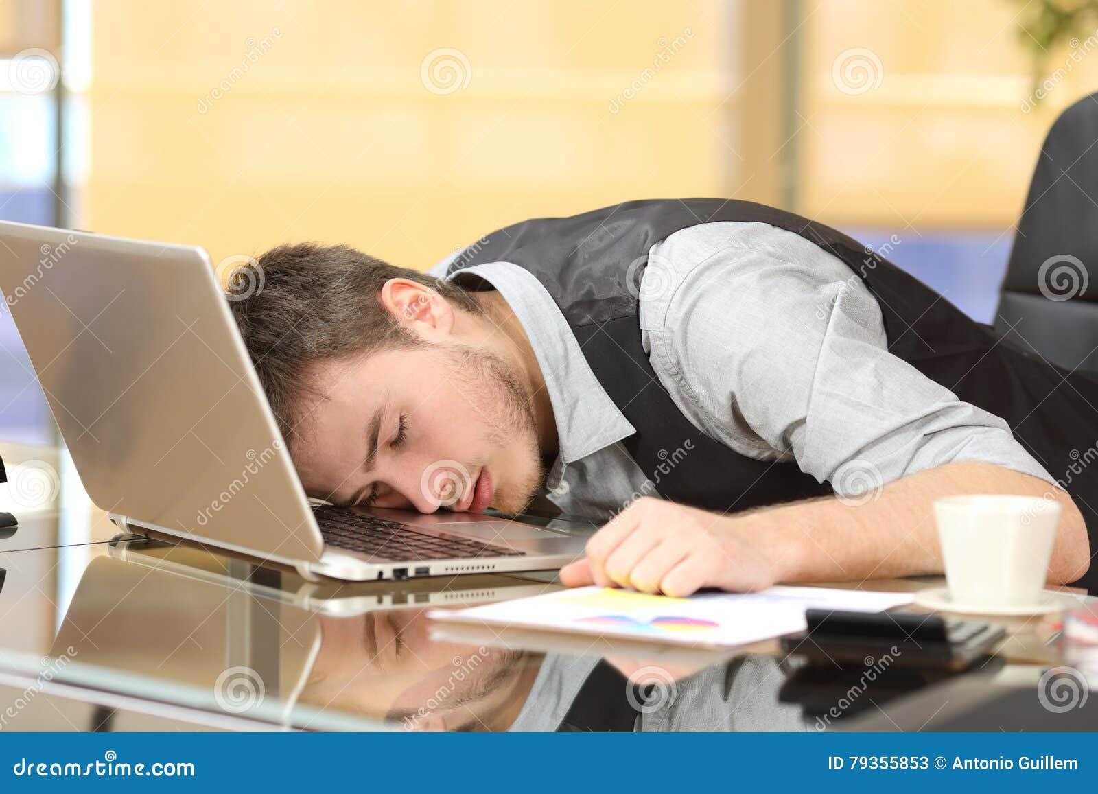 Zmęczony biznesmen śpi nad laptopem przy pracą