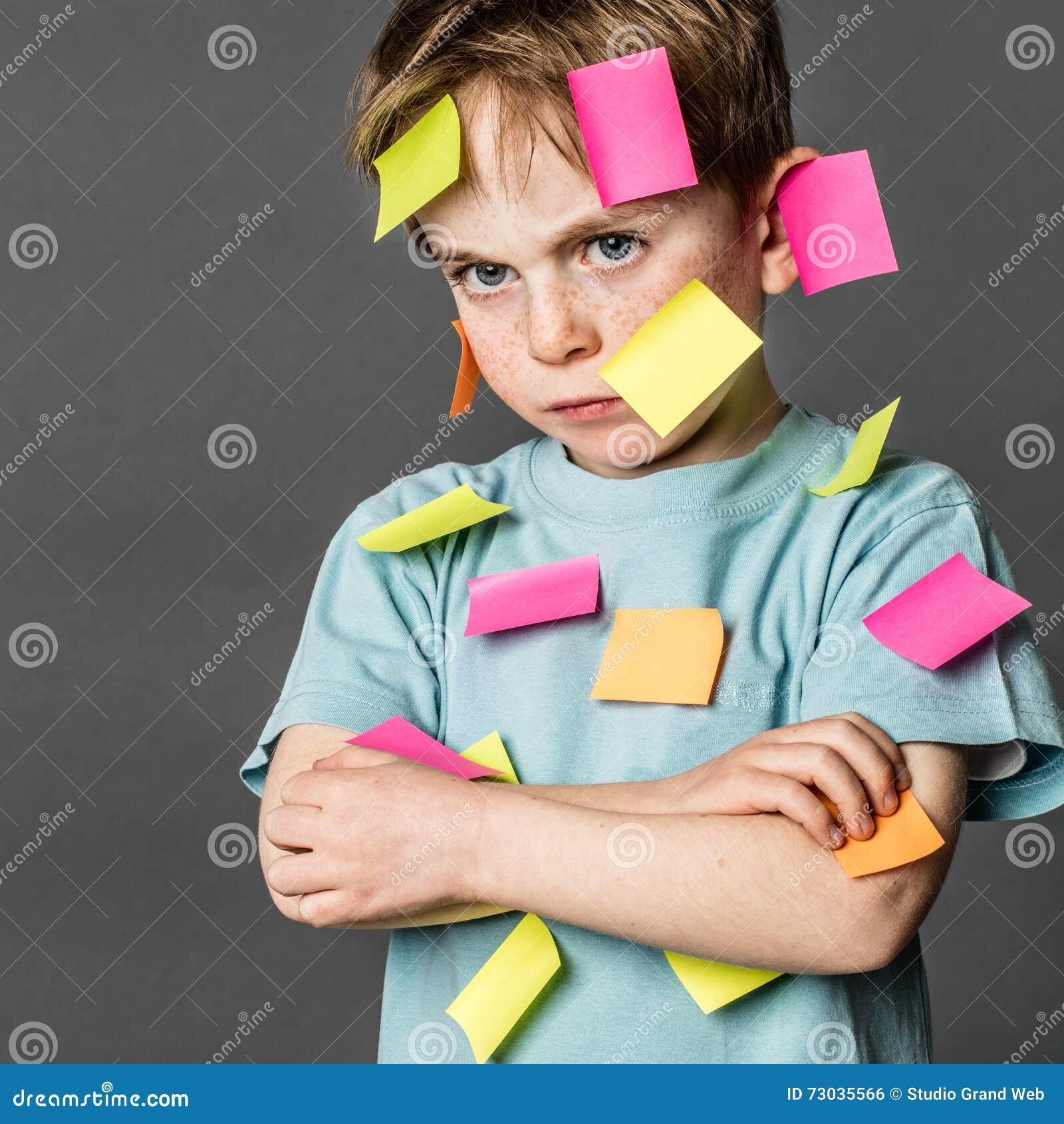 Zmęczony dzieciaka dąsanie z krzyżować rękami z notatkami na twarzy