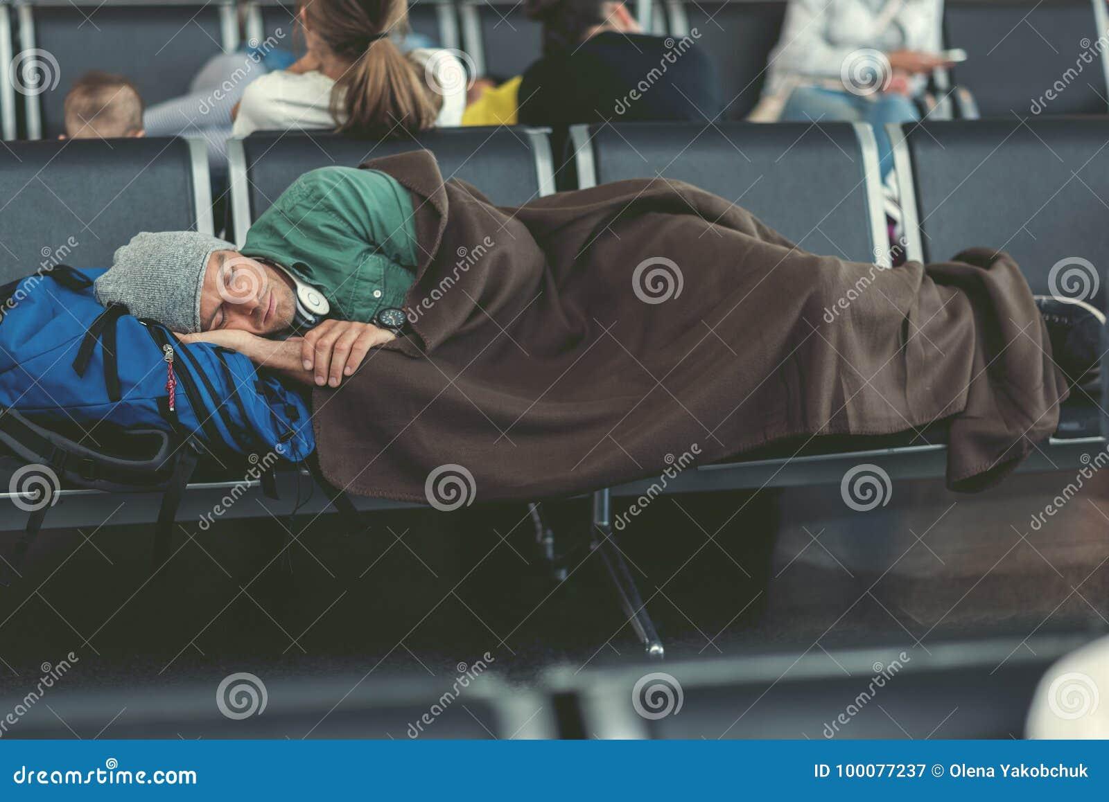 Zmęczony facet śpi w lotniskowym holu