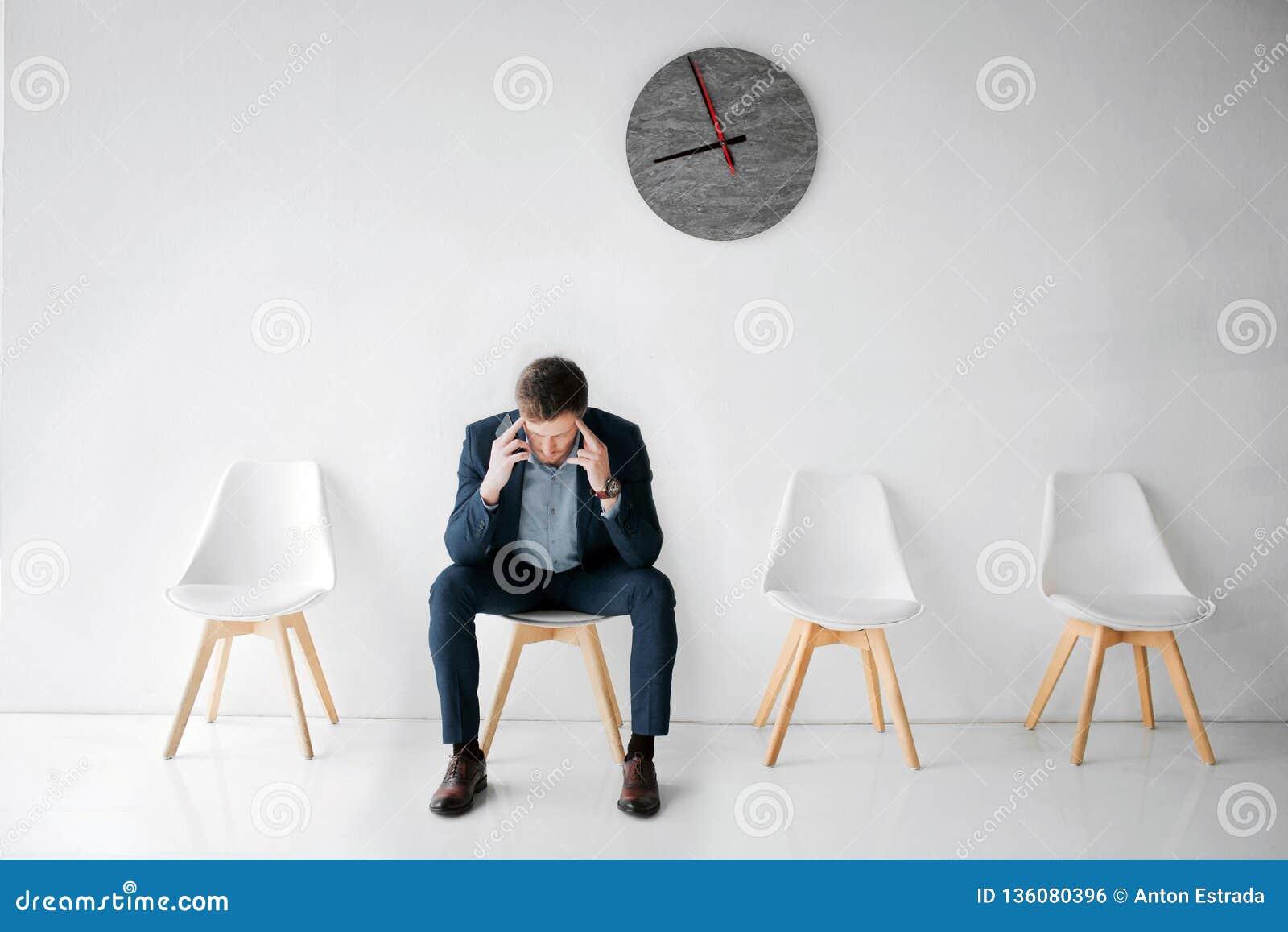 Zmęczony i skołowany młody człowiek siedzi na białym krześle na izbowy samotnym Trzyma ręki na głowie Facet migrenę Cierpi