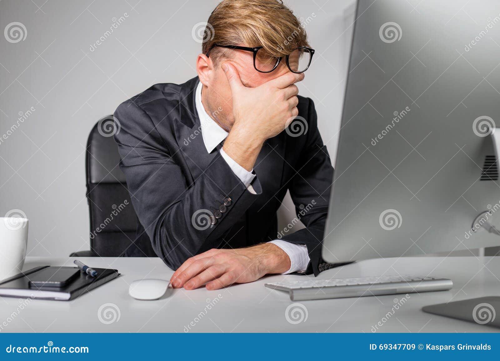 Zmęczony mężczyzna trzyma jego czoło