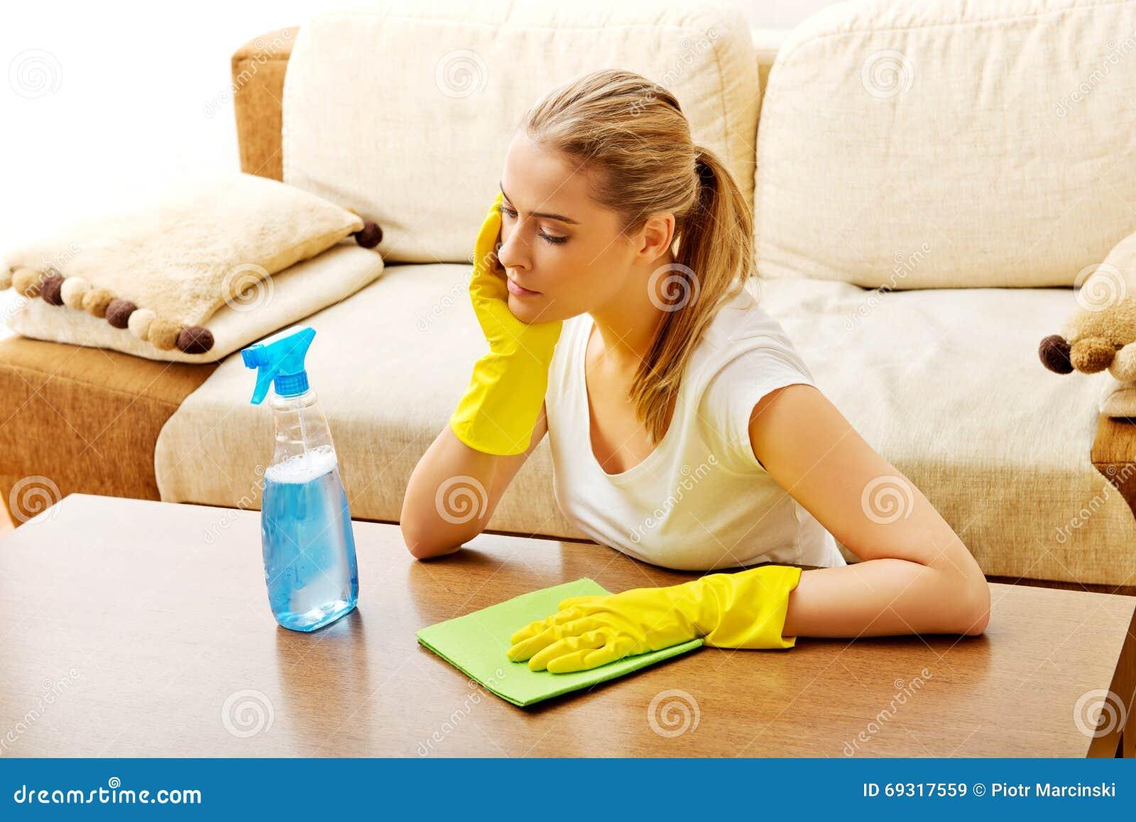 Zmęczony młodej kobiety cleaning stół w żółtych rękawiczkach