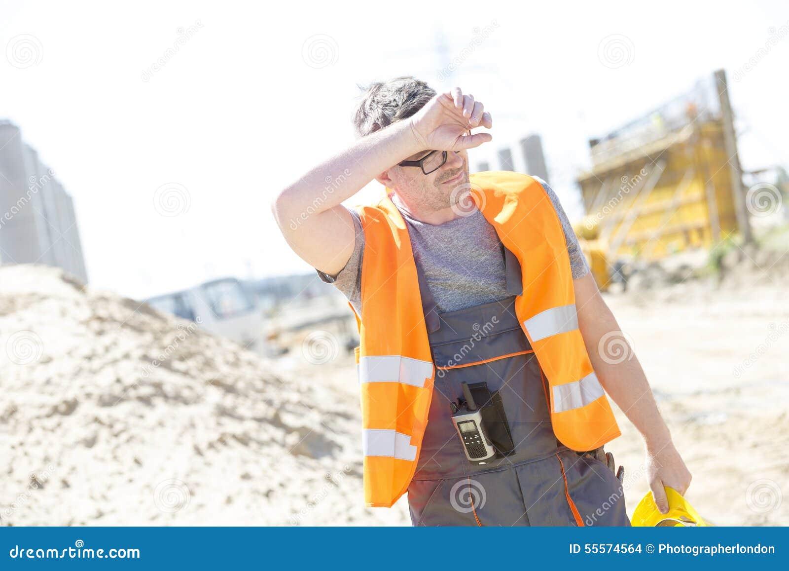 Zmęczony pracownika budowlanego obcierania czoło przy miejscem