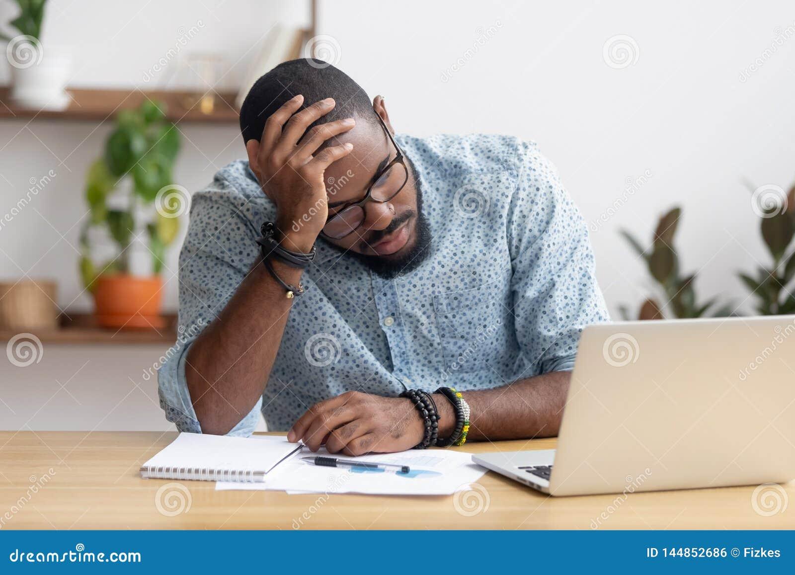 Zmęczony przygnębiony zanudzający afrykański biznesmen udaremniający biznesowym niepowodzeniem