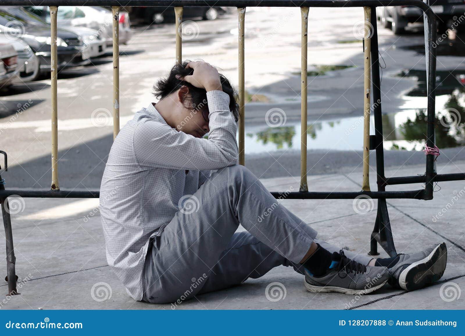 Zmęczony zaakcentowany Azjatycki biznesowego mężczyzna nakrywkowy czoło z rękami