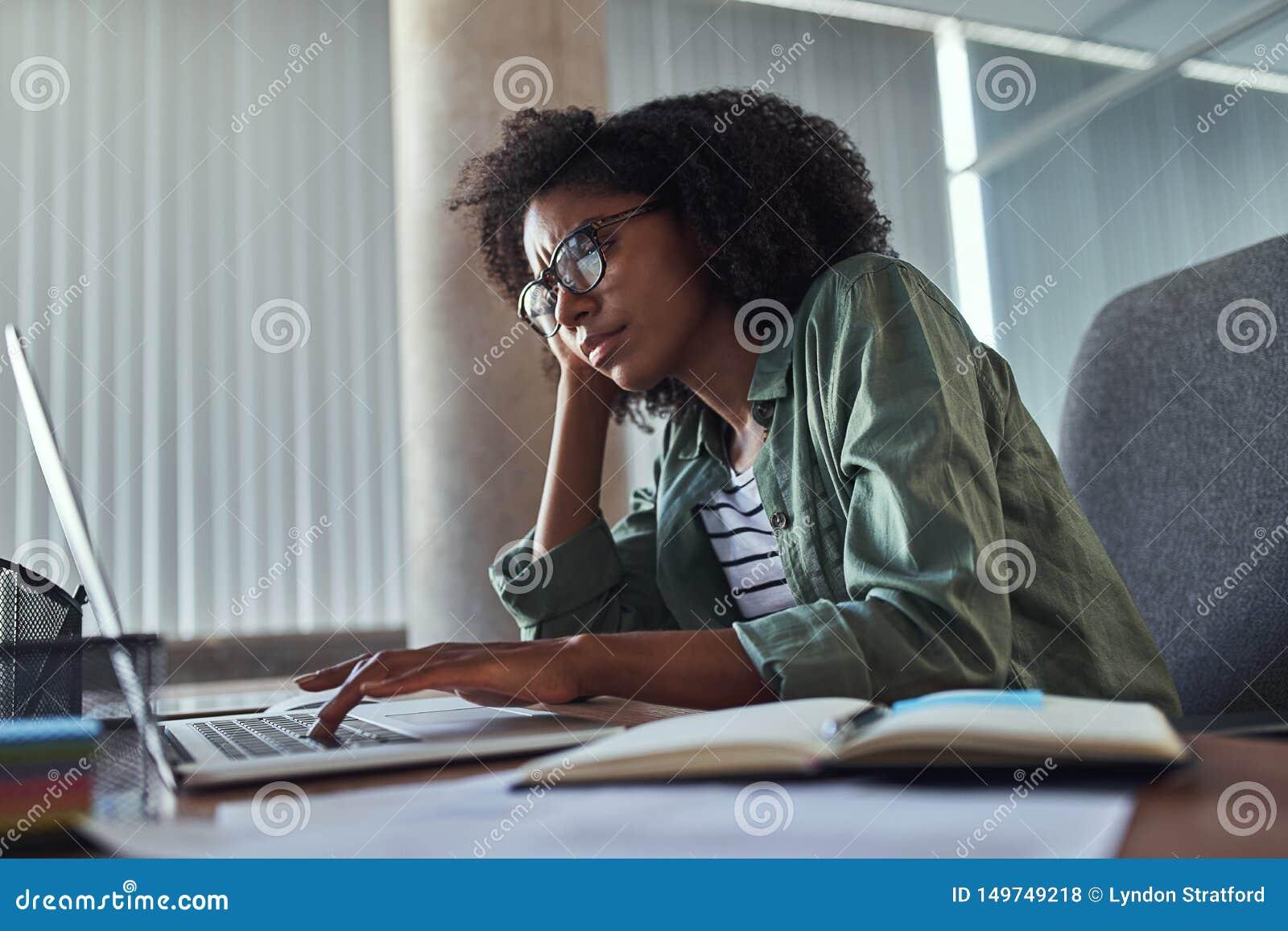 Zmartwiony młody bizneswoman używa laptop przy biurowym biurkiem