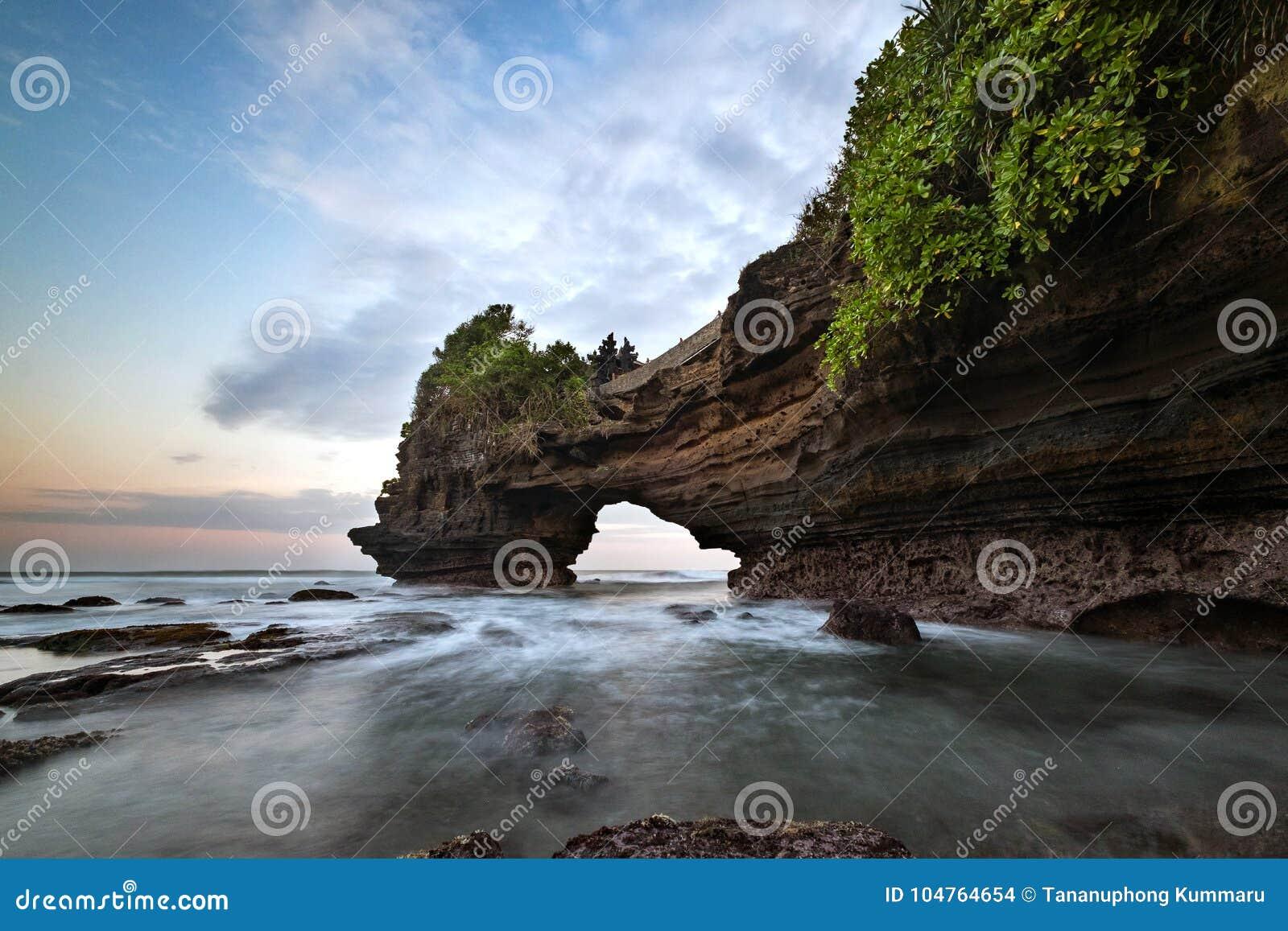 Zmierzch blisko sławnego turystycznego punktu zwrotnego Bali wyspa - Tanah Batu Bolong & udziału świątynia