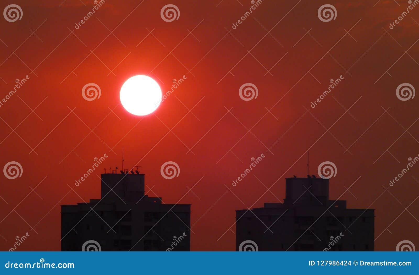 Zmierzch na czerwonym niebie nad budynkami w jesieni