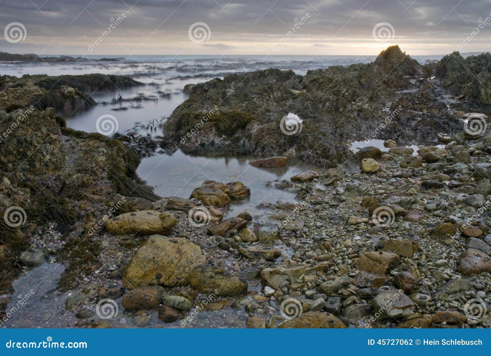 Zmierzch nad skalistej plaży wodą
