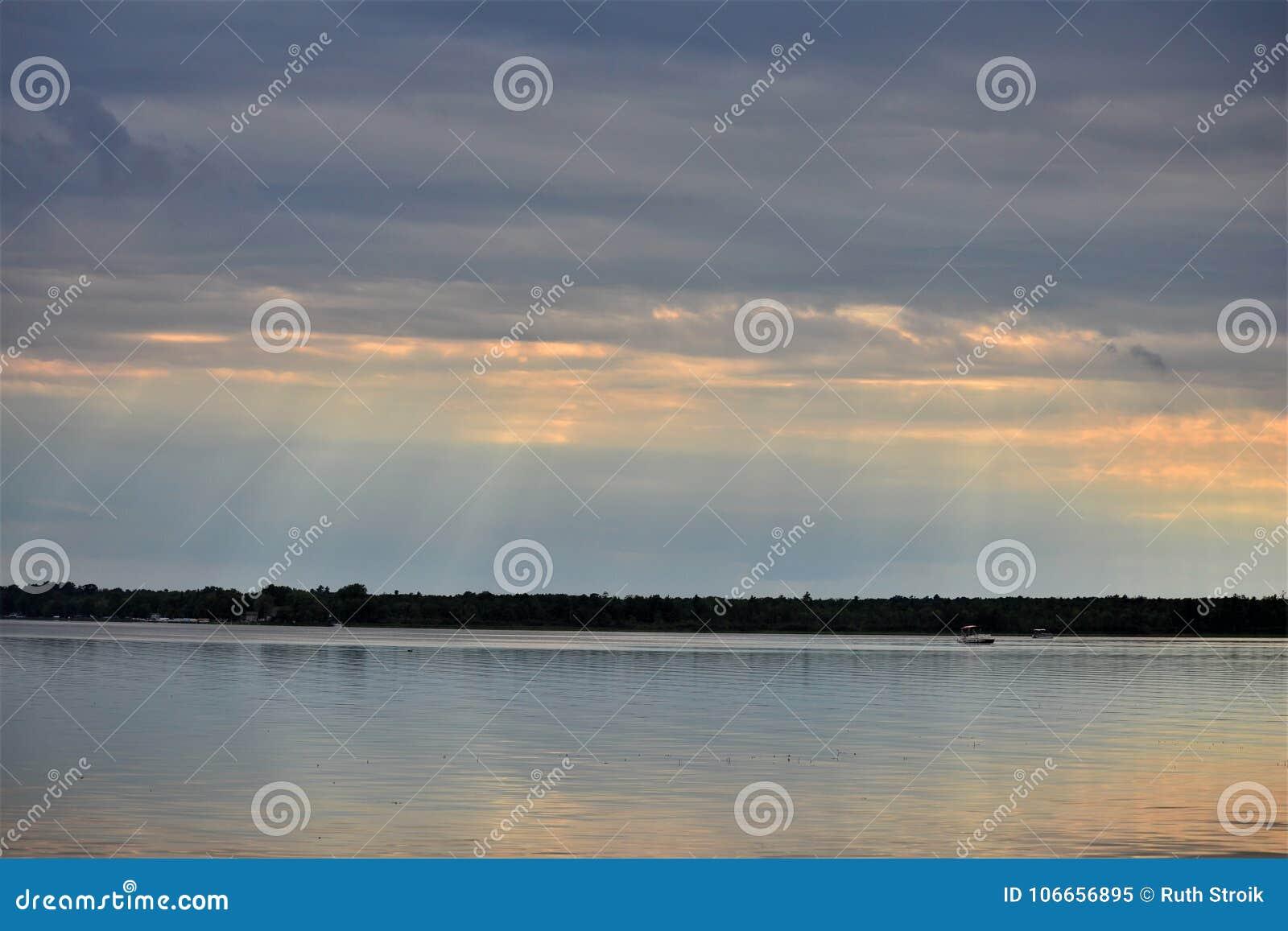 Zmierzch przez chmurzących nieb nad Shawano jeziorem w Wisconsin
