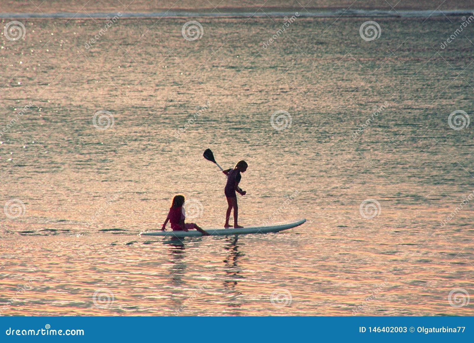 Zmierzch scena na tle Dwa małej dziewczynki sylwetki padddling