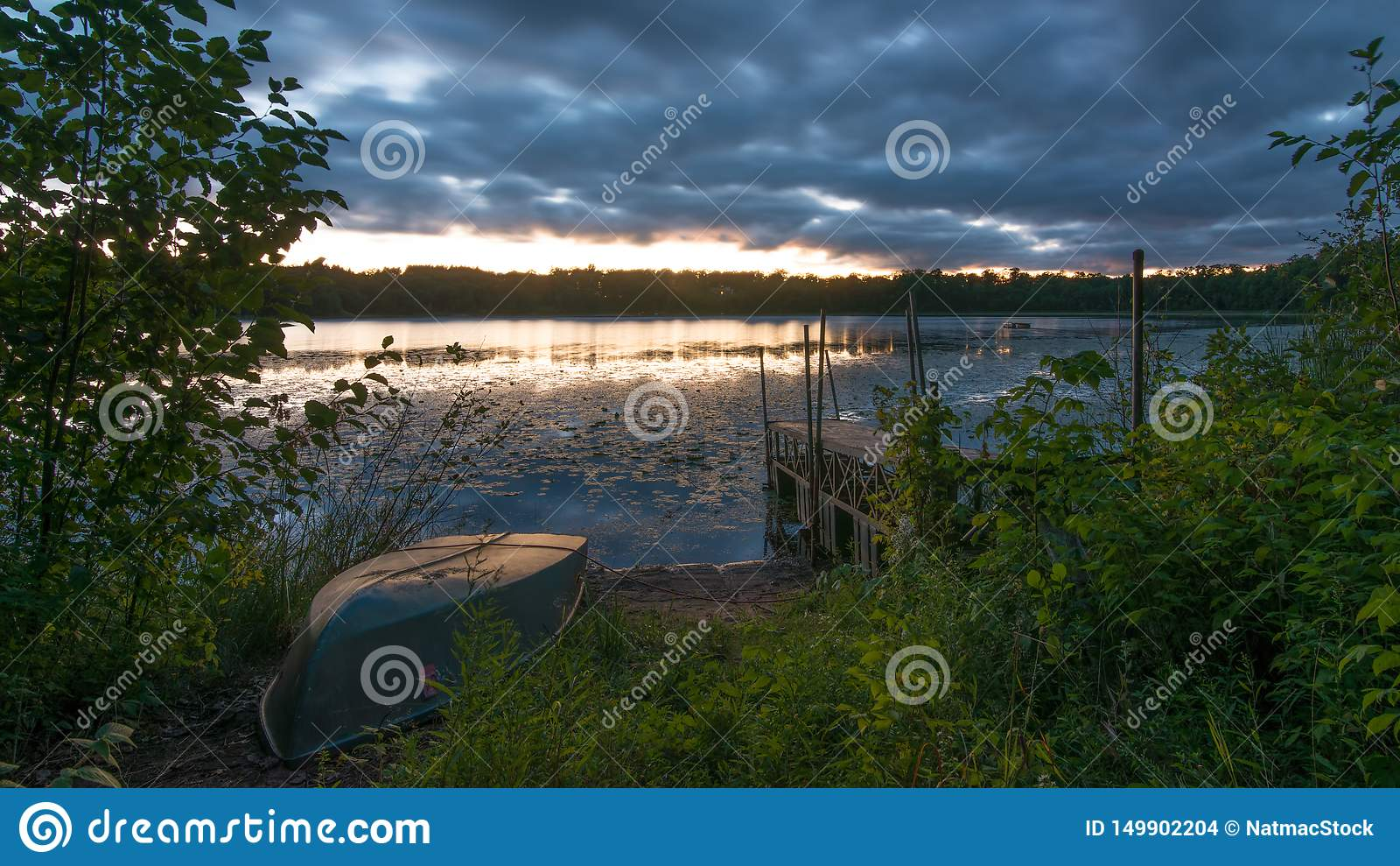 Zmierzch z starym dokiem i starą rząd łodzią na małym dalekim jeziorze w Północnym Wisconsin chmury wewnątrz i pogodowy przybycie