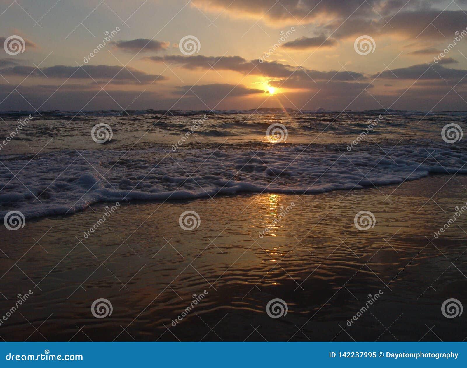 Zmierzchu widok na spokojnej piaskowatej plaży z chmurnym niebem i złotym światłem