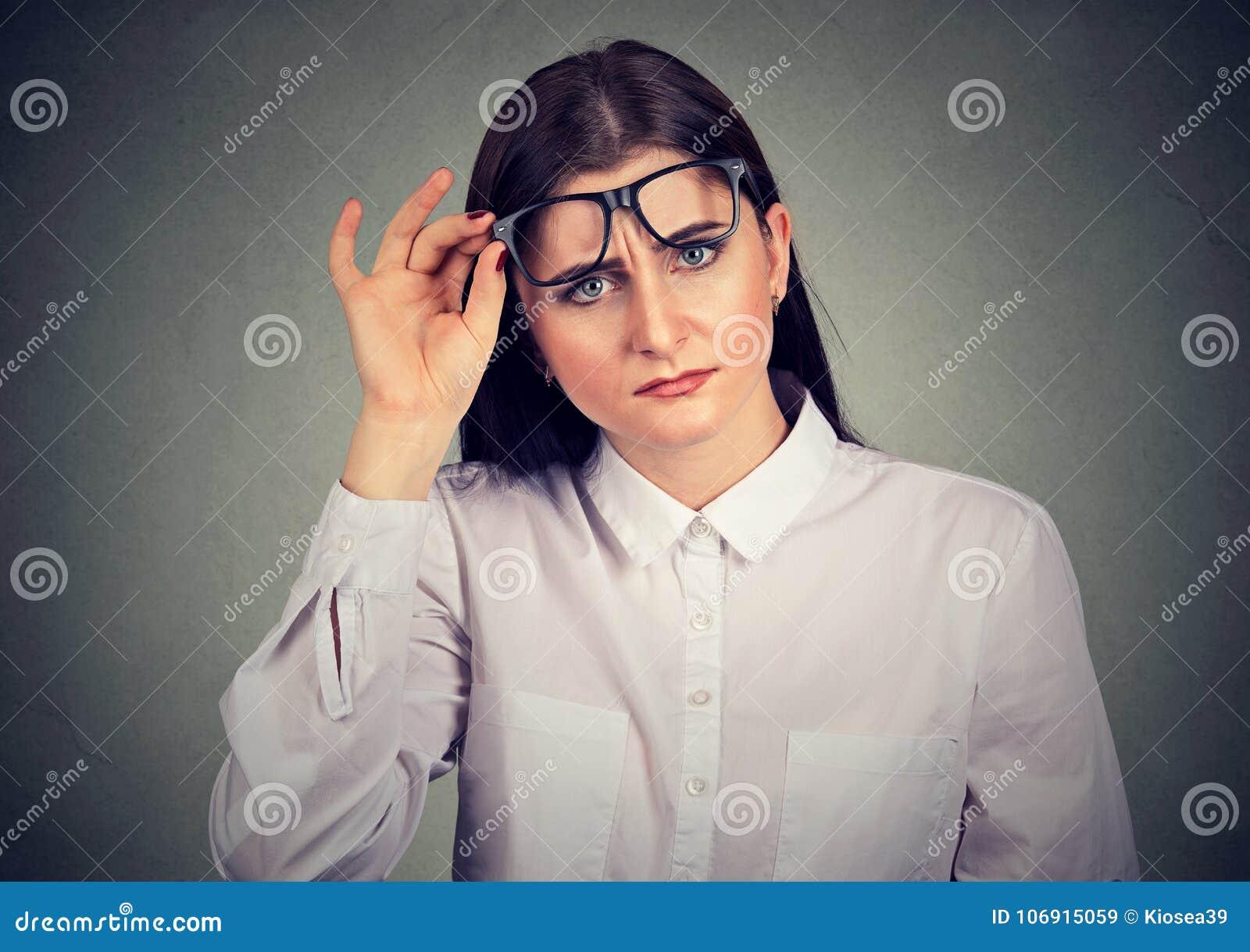 Zmieszana kobieta patrzeje przez eyeglasses