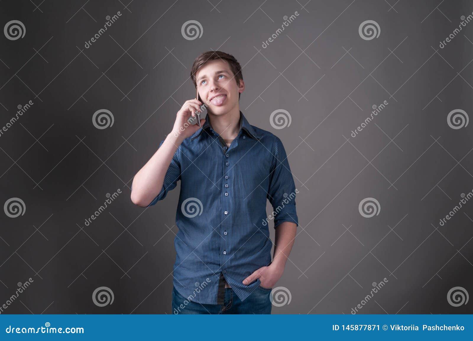 Zmieszany przystojny młody człowiek opowiada na smartphone w błękitnej koszula z wtykać za jęzorze