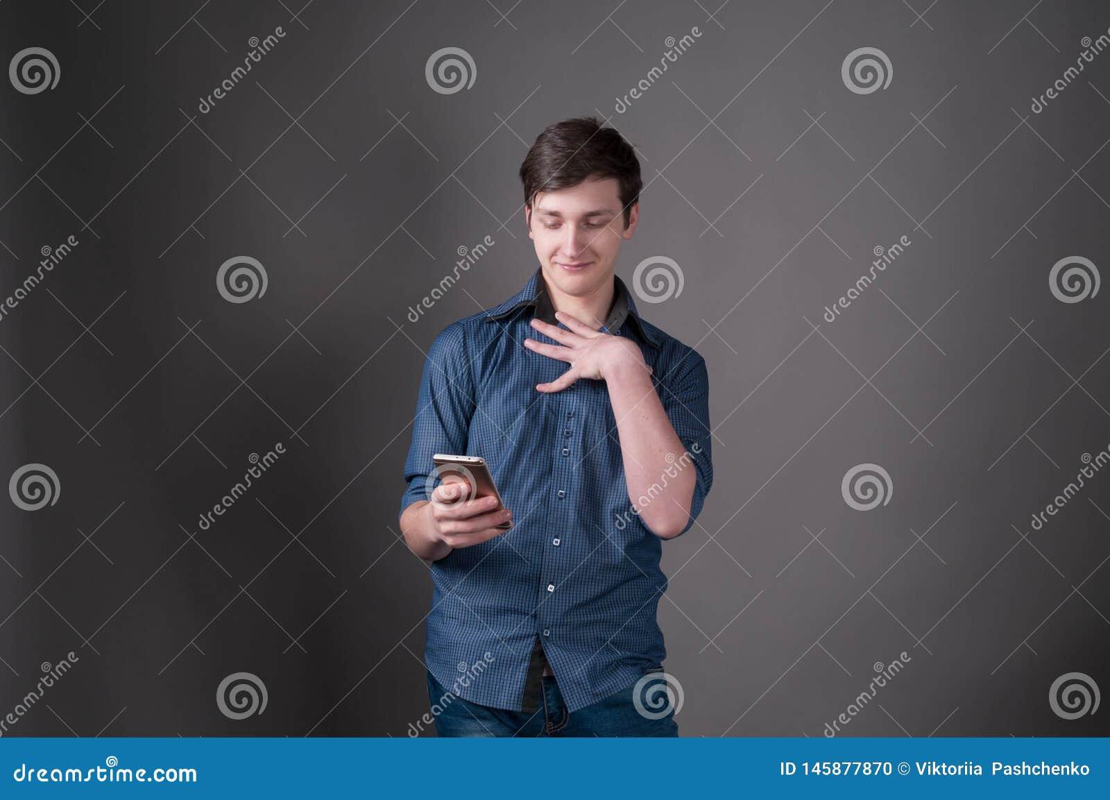 Zmieszany przystojny młody człowiek w błękitnym koszulowym uśmiechniętym i patrzeje smartphone na popielatym tle