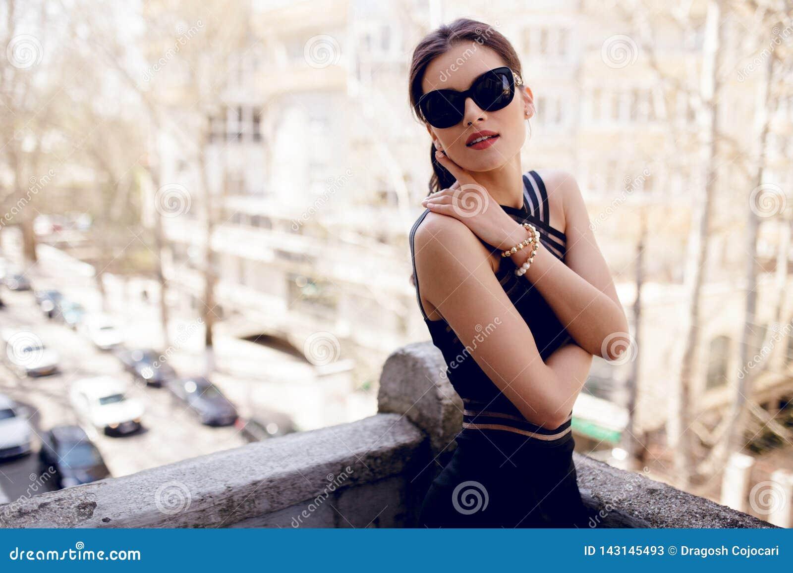 Zmysłowa, brunetka kobieta w okularach przeciwsłonecznych, seksowna czerni suknia, włosiany ponytail i piękna twarz,