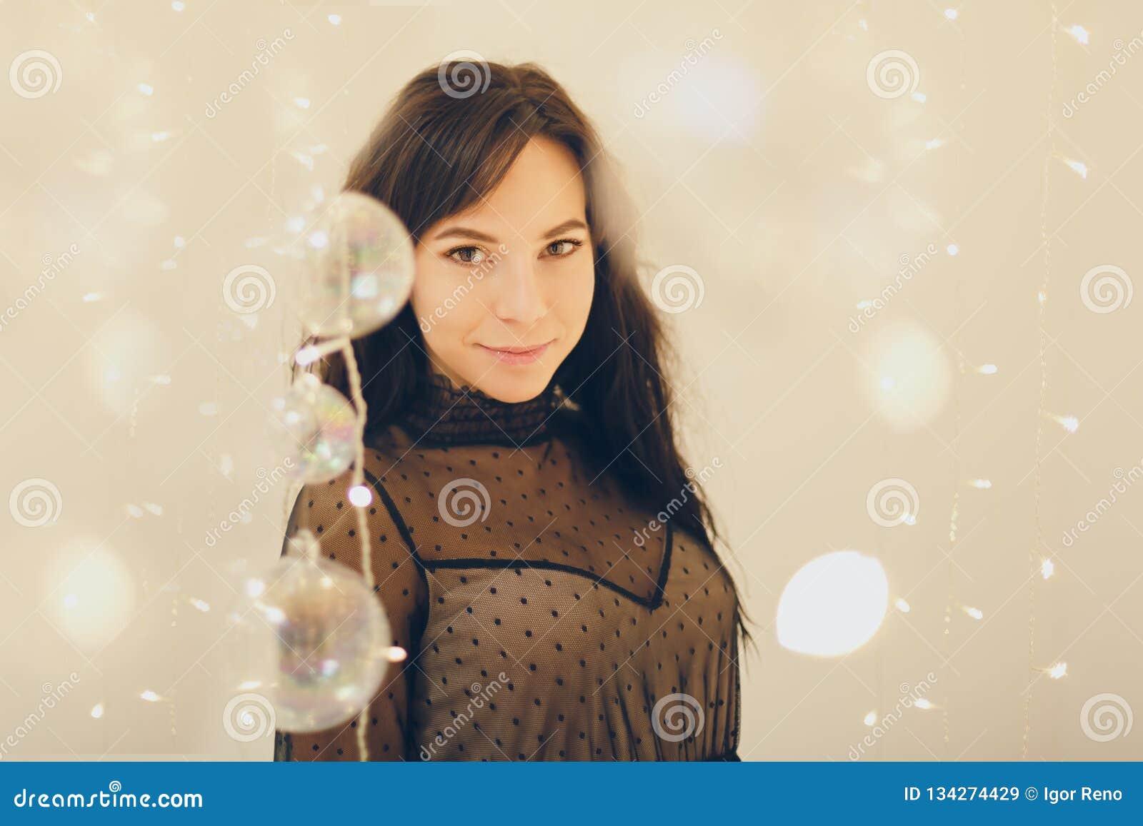 Zmysłowa młoda kobieta zostaje uśmiechnięty nad światła tłem w koktajl sukni