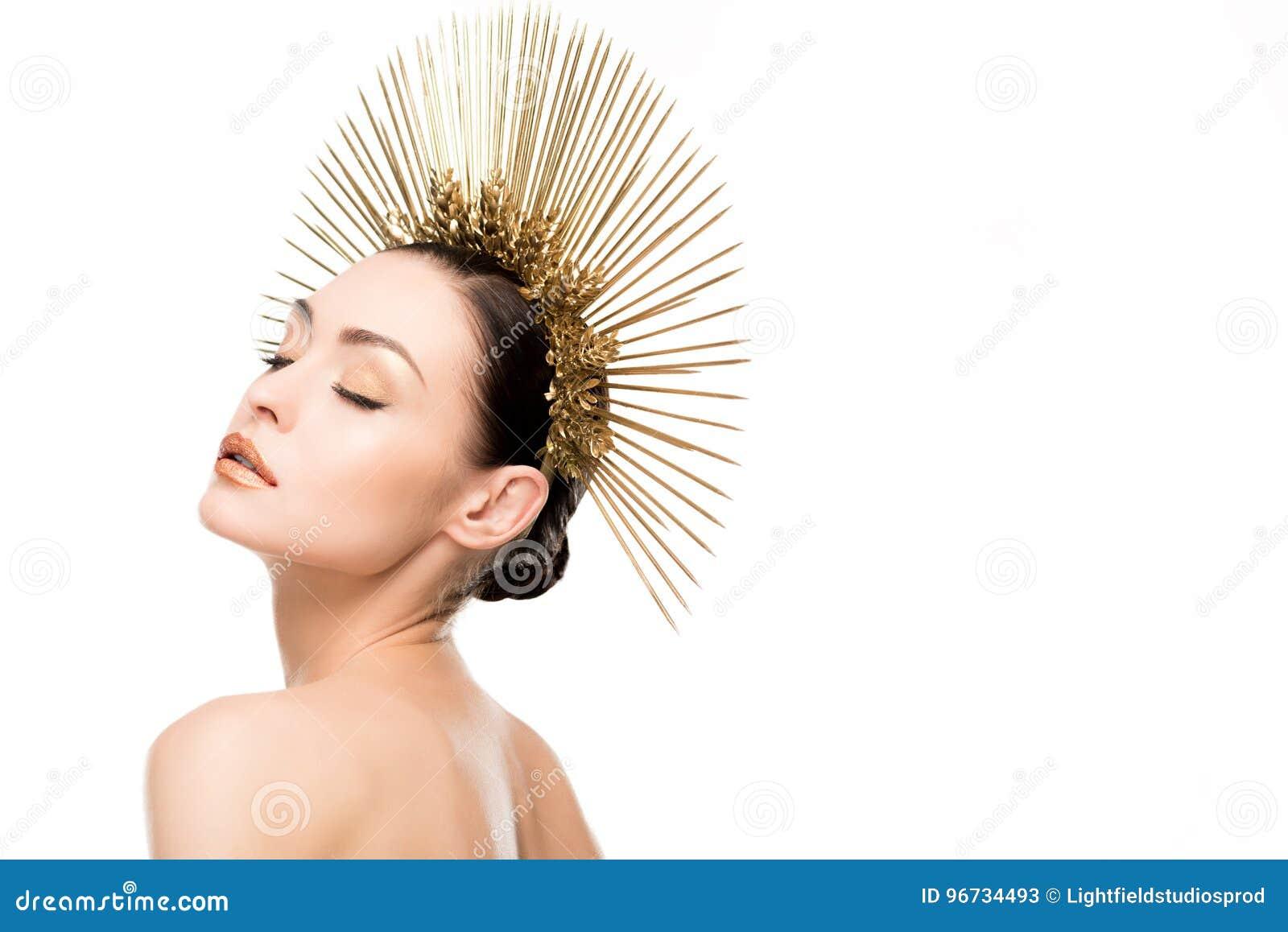Zmysłowa naga kobieta jest ubranym złotego headpiece z zamkniętymi oczami