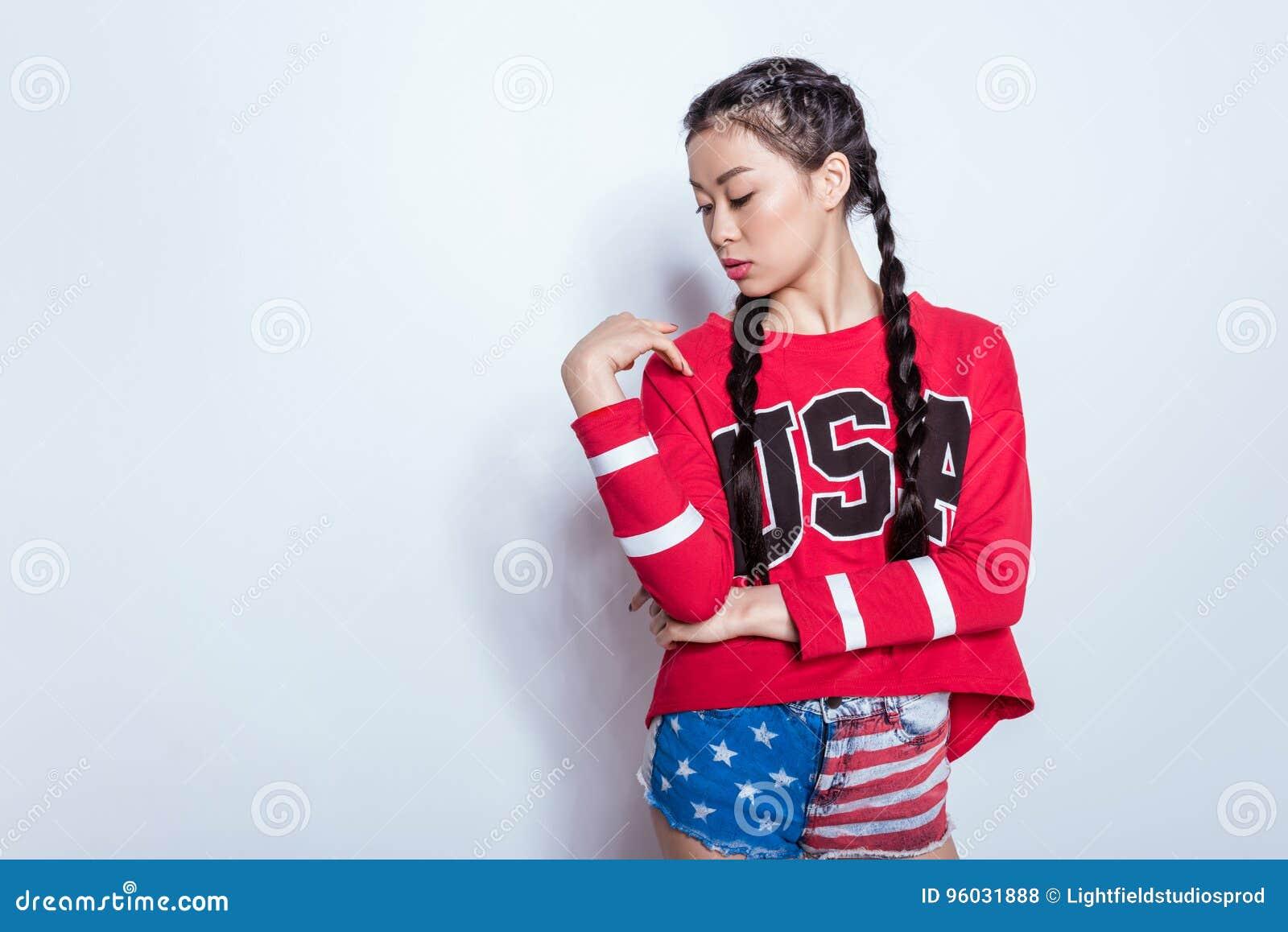 Zmysłowego eleganckiego modnisia azjatykcia dziewczyna w amerykańskim patriotycznym stroju odizolowywającym na popielatym