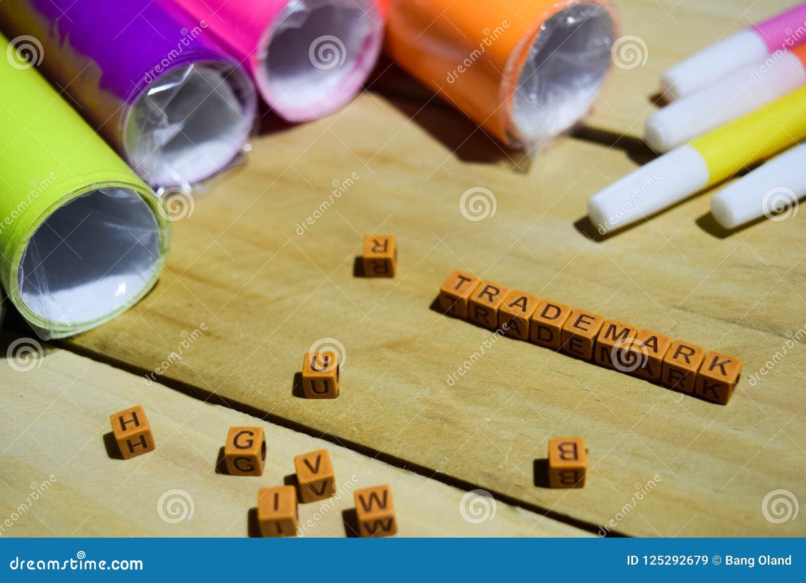 Znak firmowy na drewnianych sześcianach z kolorowym papierem i pióro, pojęcie inspiracja na Drewnianym tle